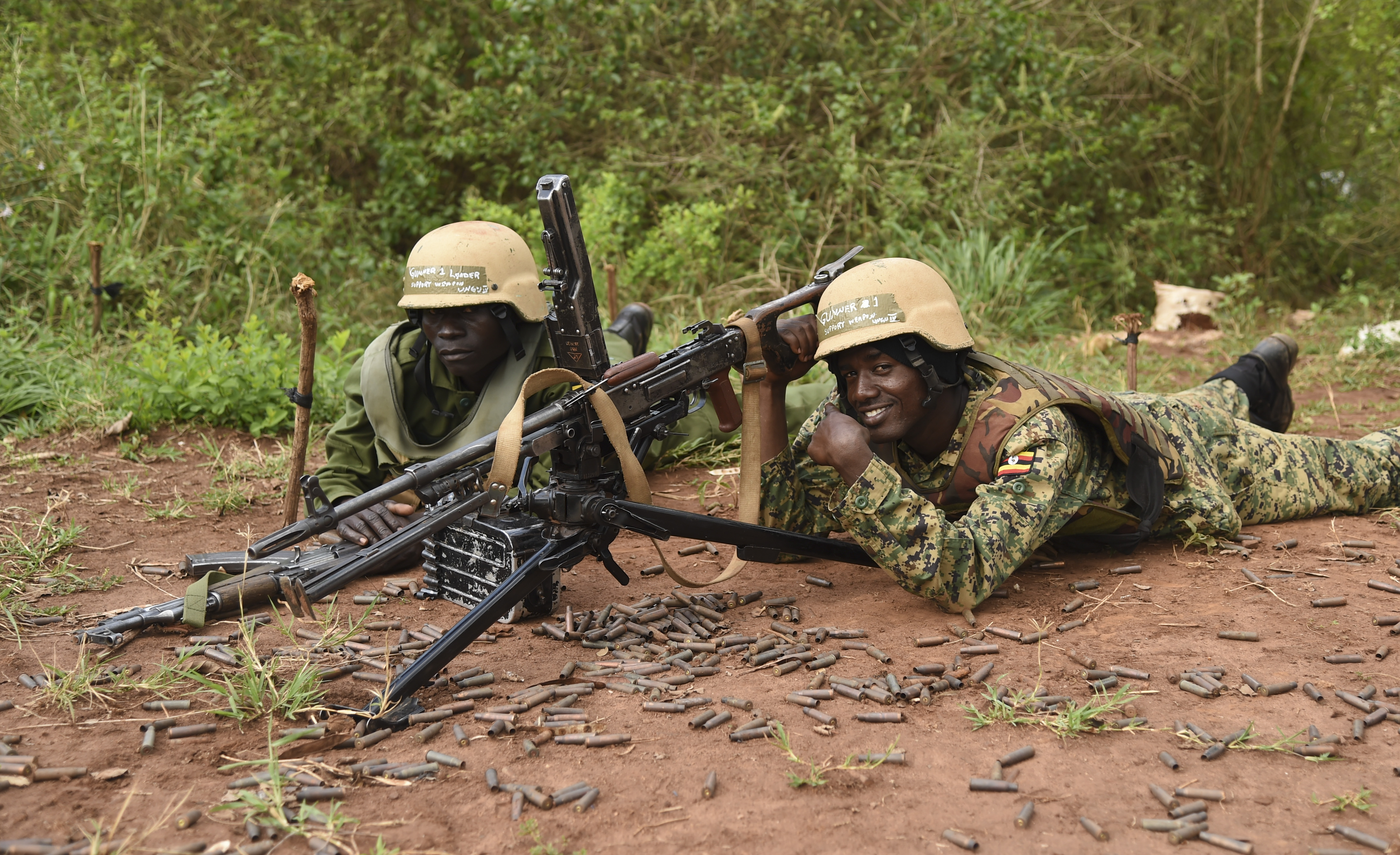 Uganda People's Defense Force soldiers, Ugandan Battle Group 22 (UGABAG 22), wait behind their weapons after a live fire exercise at Camp Singo, Uganda, Feb. 27, 2017. UGABAG 22 will perform common task training, a combat lifesaver course, counter improvised-explosive-device training, and live fire training as a part of their pre-deployment preparation. (U.S. Air National Guard photo by Staff Sgt. Penny Snoozy)