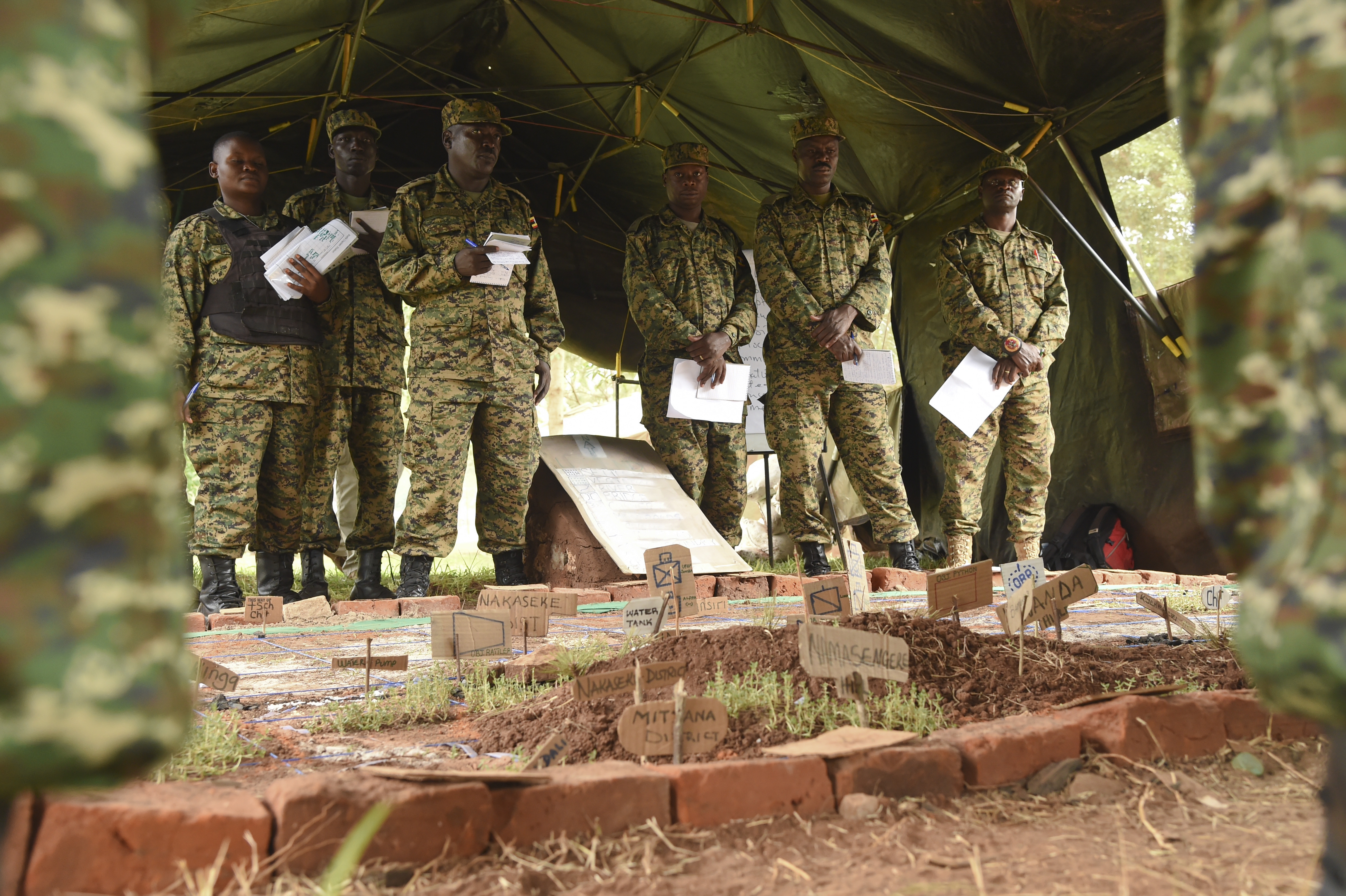 Uganda People's Defense Force (UPDF) soldiers receive a briefing over a terrain model at Camp Singo, Feb. 28, 2017. The UPDF's Ugandan Battle Group 22 received pre-deployment training from allied forces and subject matter experts to increase their readiness and better prepare forces to respond to issues in their region. (U.S. Air National Guard photo by Staff Sgt. Penny Snoozy)