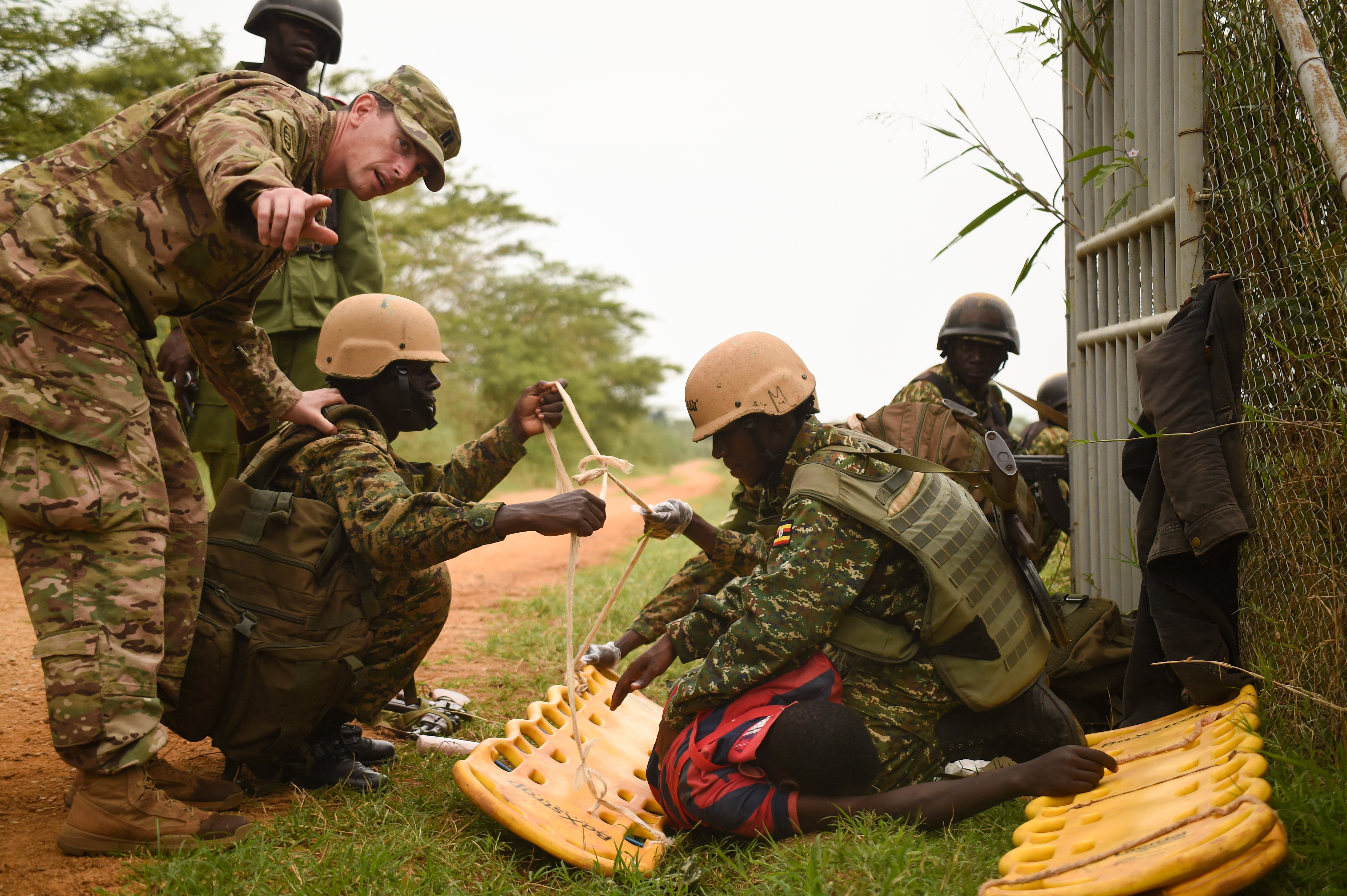 U.S. Army Capt. Brandon Resor with Combined Joint Task Force-Horn of Africa's (CJTF-HOA), 418th Civil Affairs Battalion, directs Uganda People's Defense Force (UPDF) soldiers assigned to Ugandan Battle Group 22, as they prepare a simulated casualty for transport during a medical exercise at Camp Singo, Uganda, March 3, 2017. CJTF-HOA members assisted UPDF soldiers assigned to Ugandan Battle Group 22 to employ skills acquired from their predeployment training such as nine-line medical evacuation, combat lifesaving techniques and casualty extraction. (U.S. Air National Guard photo by Staff Sgt. Penny Snoozy)