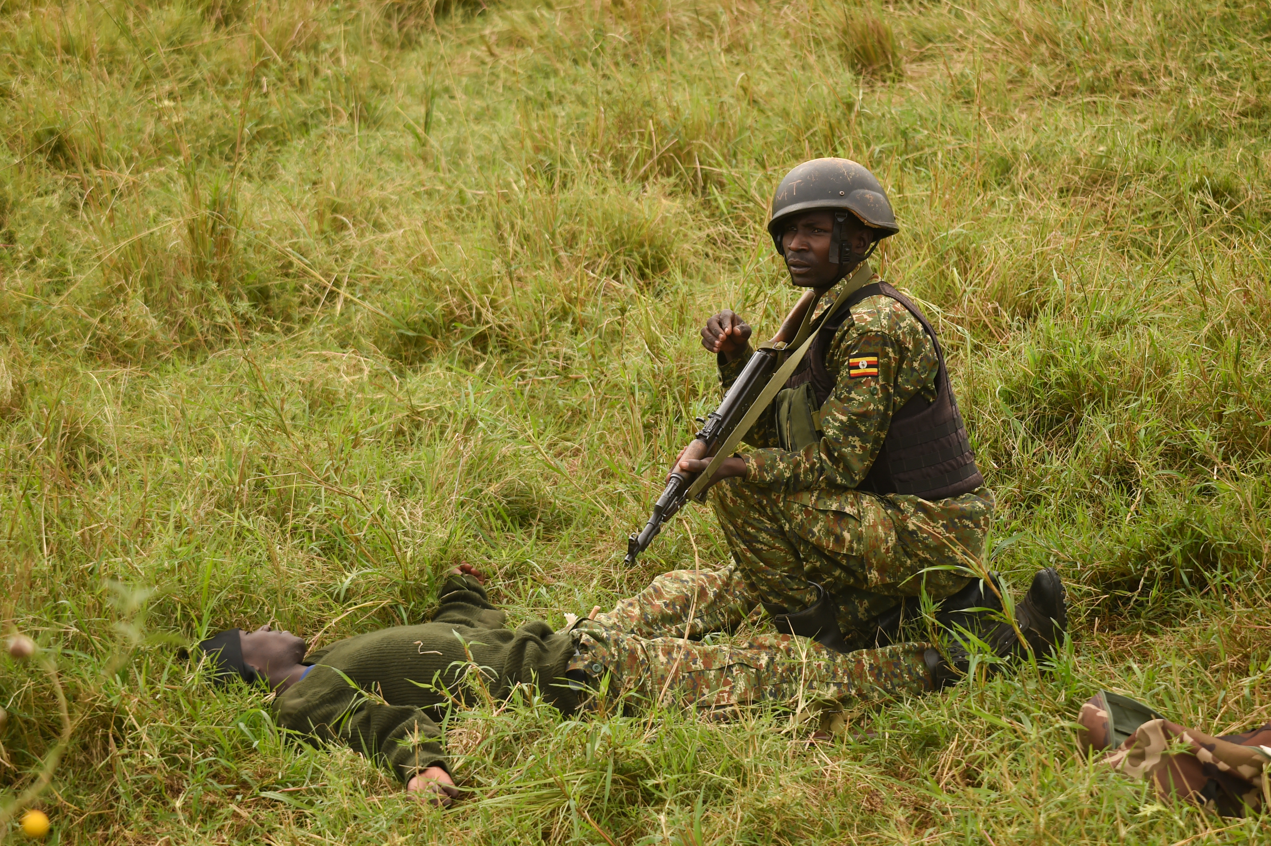 A Uganda People's Defense Force (UPDF) soldier with Ugandan Battle Group 22, scans the area before applying a tourniquet during a medical exercise at Camp Singo, Uganda, March 3, 2017. Up to 25 percent of deaths on the battlefield are preventable. Administering swift medical attention on the battlefield and in transport greatly improves the survival rate of casualties. (U.S. Air National Guard photo by Staff Sgt. Penny Snoozy)