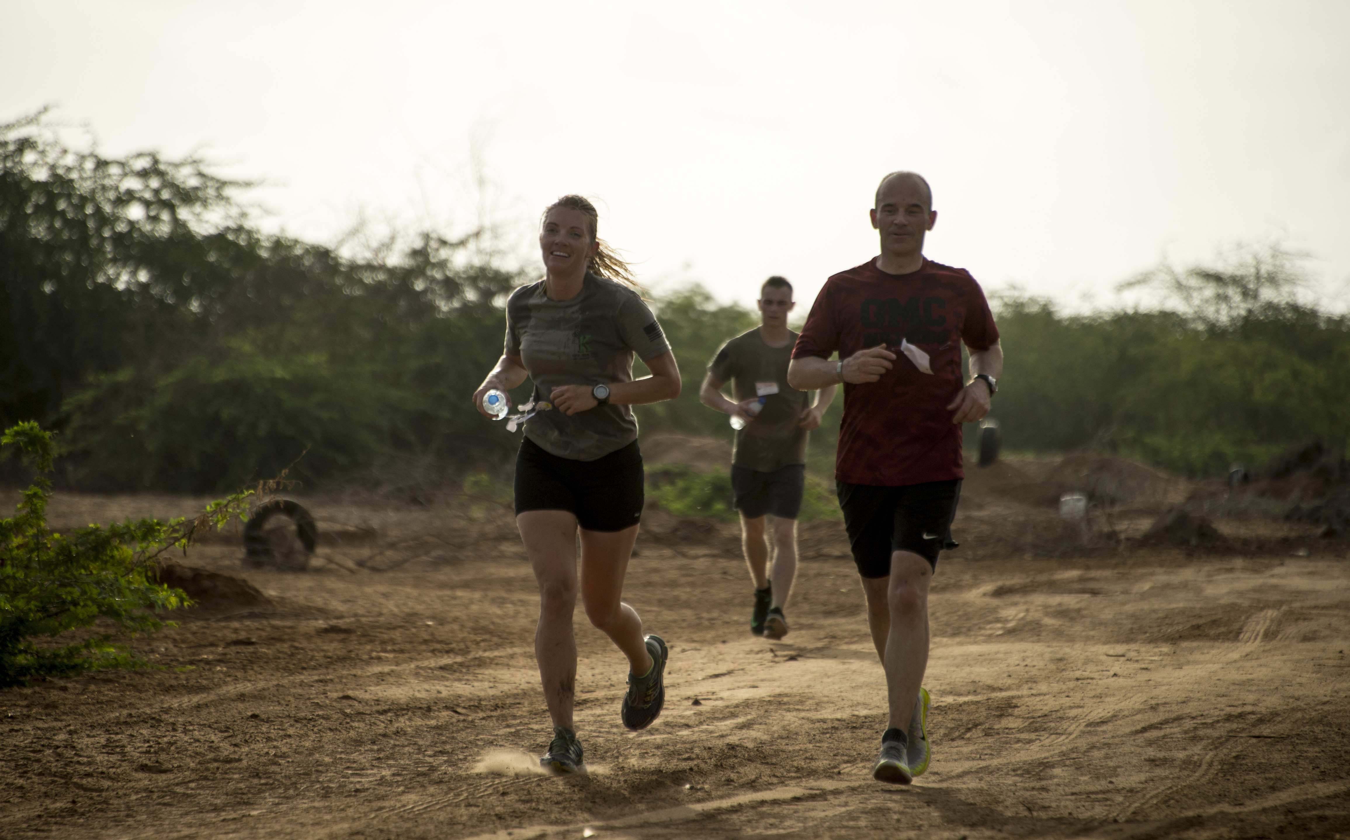 U.S. Air Force 1st Lt. Elizabeth Holloway and U.S. Army Col. Jason Musteen participate in the running portion of the Joint Warrior Competition (JWC) outside of Camp Lemonnier, Djibouti, March 25, 2017. Participants in the JWC test themselves physically in various events including a four kilometer timed run. (U.S. Air National Guard photo by Staff Sgt. Christian Jadot)