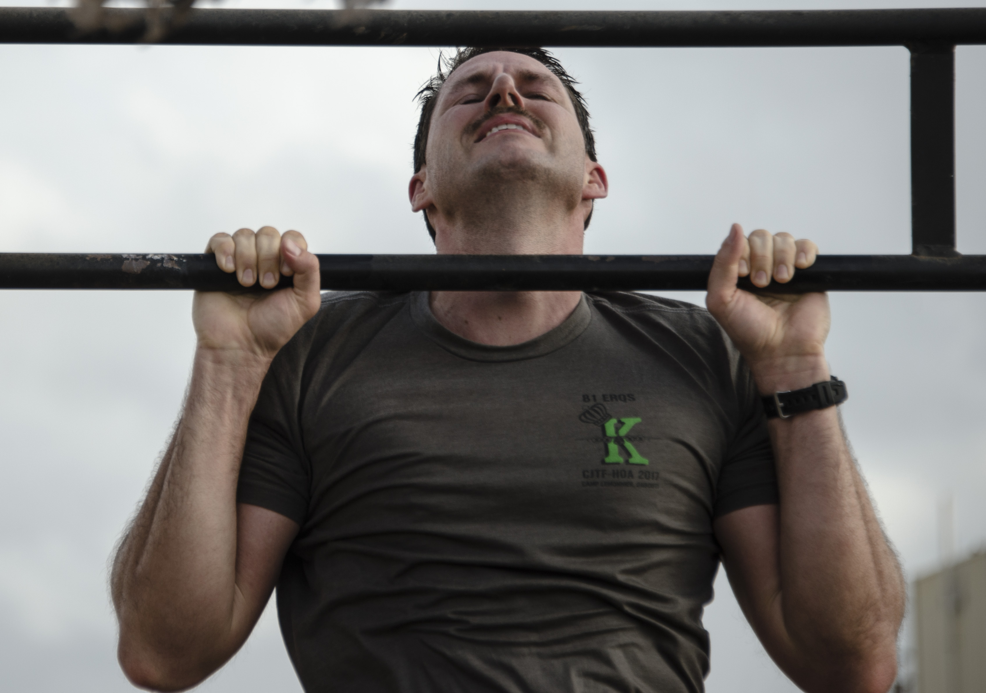 A U.S. service member participates in the pull-up portion of the Joint Warrior Competition (JWC) on Camp Lemonnier, Djibouti, March 25, 2017. Participants in the JWC test themselves physically in various events including 20 timed pull-ups. (U.S. Air National Guard photo by Staff Sgt. Christian Jadot)