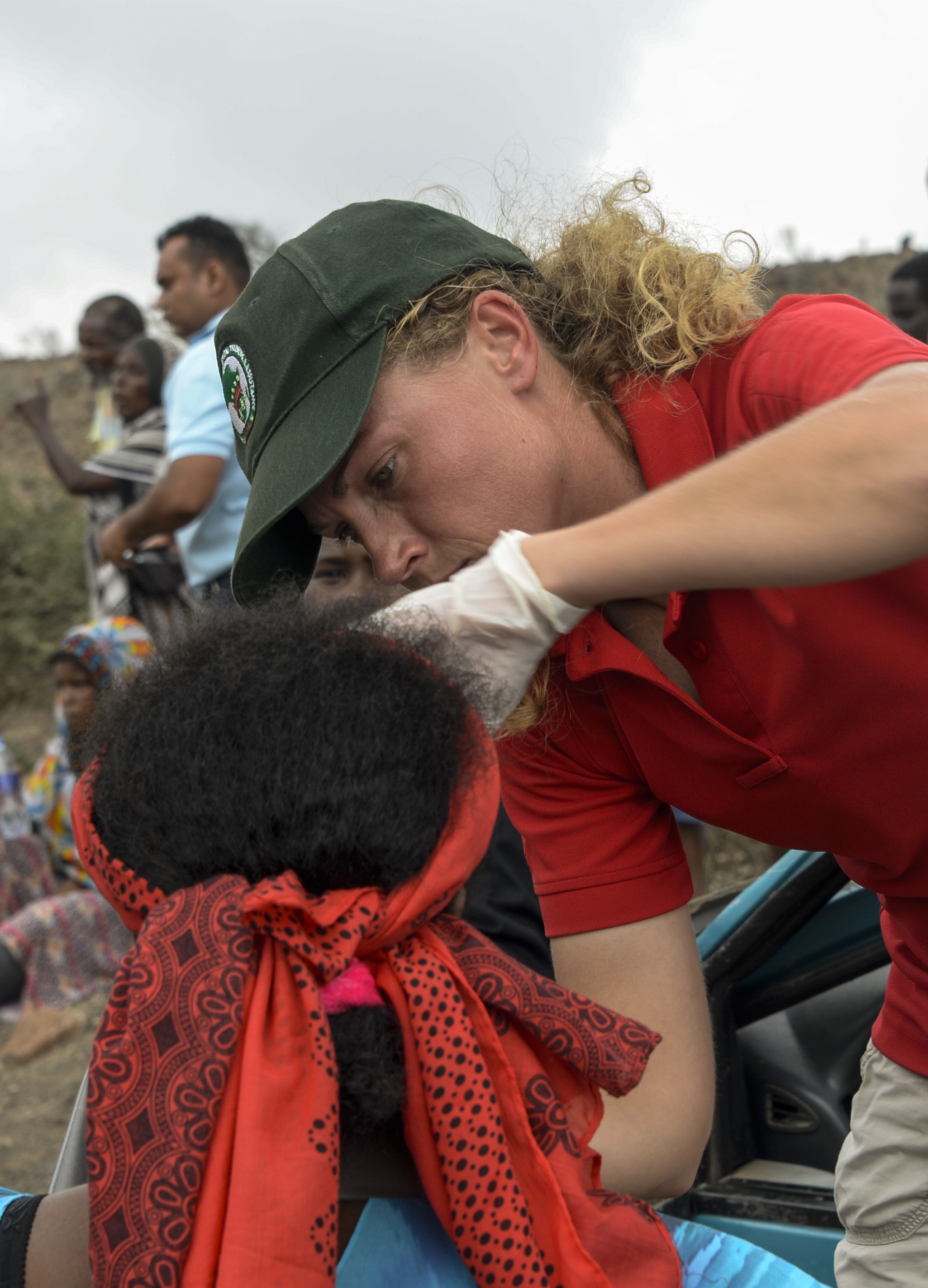 U.S. Army Sgt. Sarah DeArcy, 411th Civil Affairs Battalion medic, administers first aid to an individual involved in a vehicle accident south of We'a Djibouti, March 28, 2017. The actions of the U.S. service members resulted in the stabilization of those injured until local medical officials arrived on scene, increasing their chances of survival. (U.S. Air National Guard photo by Staff Sgt. Christian Jadot)