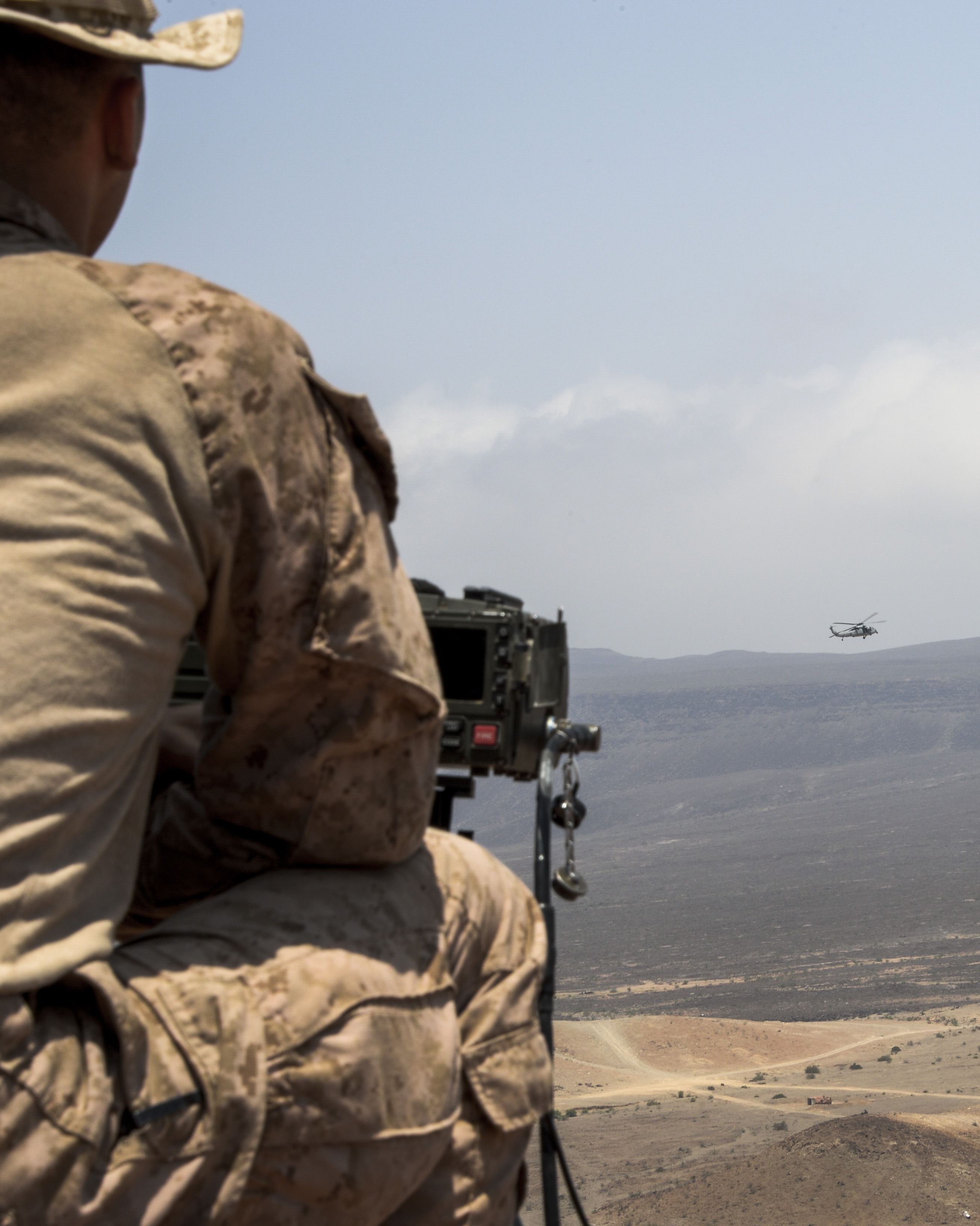 A U.S. Marine, 24th Marine Expeditionary Unit (24th MEU), activates a targeting laser to guide a U.S. Navy SH-60 Seahawk on an attack run during Exercise Alligator Dagger at Arta Plage, Djibouti, April 9, 2017. Alligator Dagger provides a unique opportunity to enhance capabilities in critical mission sets inherent to the U.S. Navy-Marine Corps team. (U.S. Air National Guard photo by Staff Sgt. Christian Jadot)