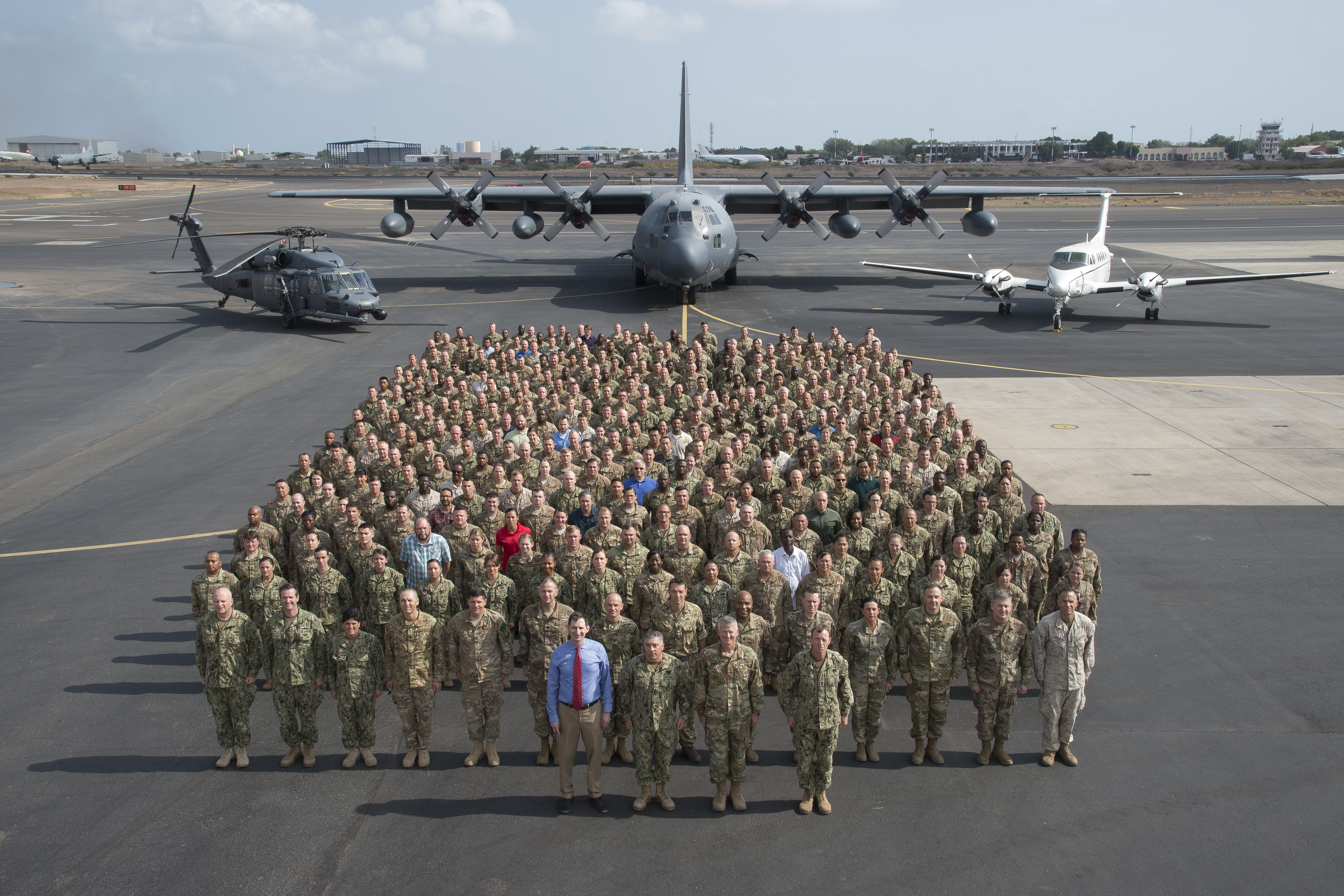U.S. Soldiers, Sailors, Airmen, Marines, DoD civilians, and contractors representing more than 2,000 members assigned to Combined Joint Task Force-Horn of Africa assemble on the flight line at Camp Lemonnier in Djibouti, April 14, 2017. CJTF-HOA Commanding General Maj. Gen. Kurt Sonntag and Command Senior Enlisted Leader Command Master Chief Geoffrey Steffee, will conclude their tour after a change of command ceremony on April 28. (U.S. Air National Guard photo by Master Sgt. Paul Gorman)