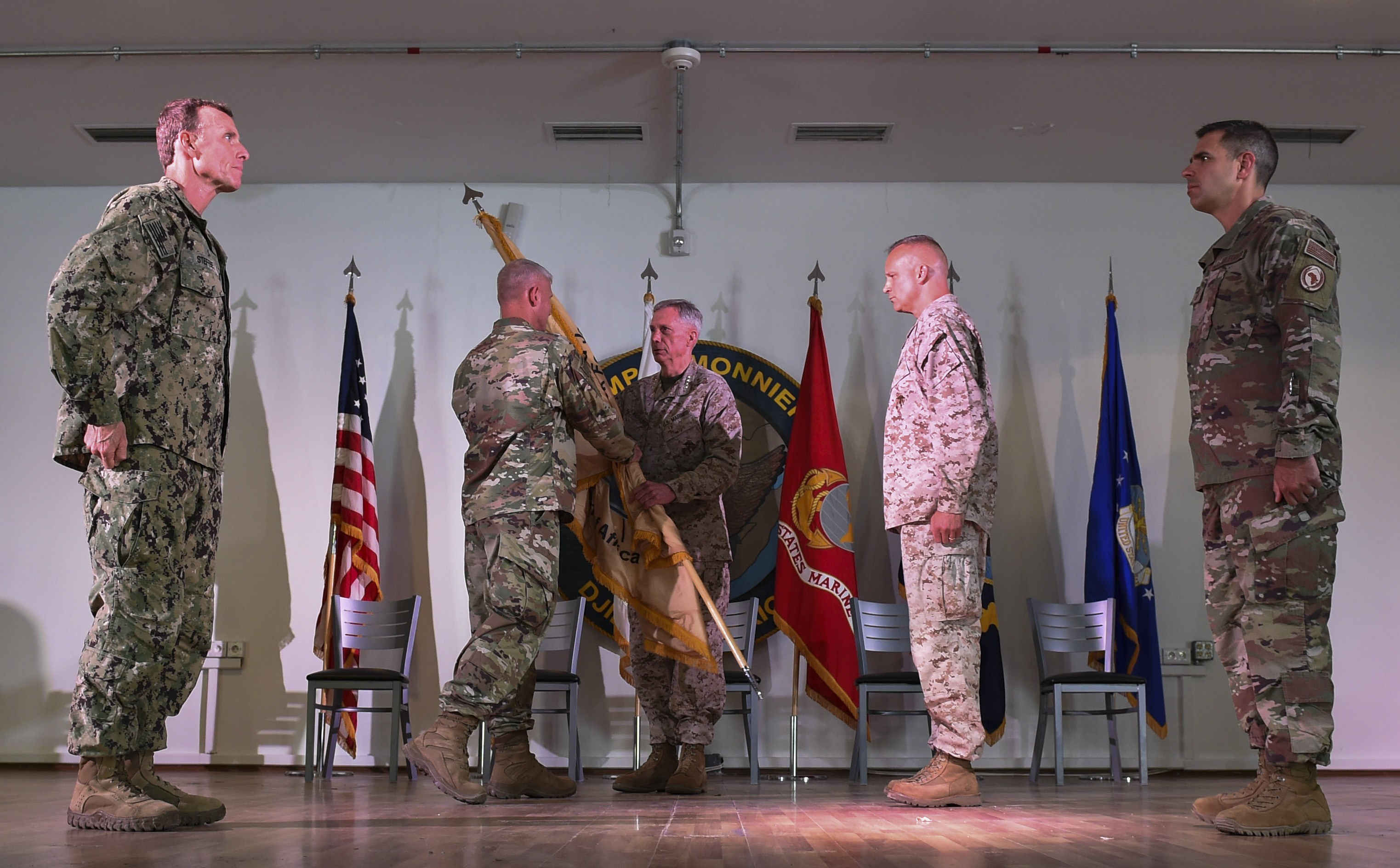 U.S. Army Maj. Gen. Kurt L. Sonntag, the outgoing Combined Joint Task Force - Horn of Africa commander, hands the guidon to U.S. Marine Corps Gen. Thomas Waldhauser, U.S. Africa Command commander, during the change of command ceremony on Camp Lemonnier in Djibouti, April 28, 2017. A prime component of the CJTF-HOA mission is to help build the defense capability and capacity among its East African partners. (U.S. Air Force Photo by Eboni Prince)