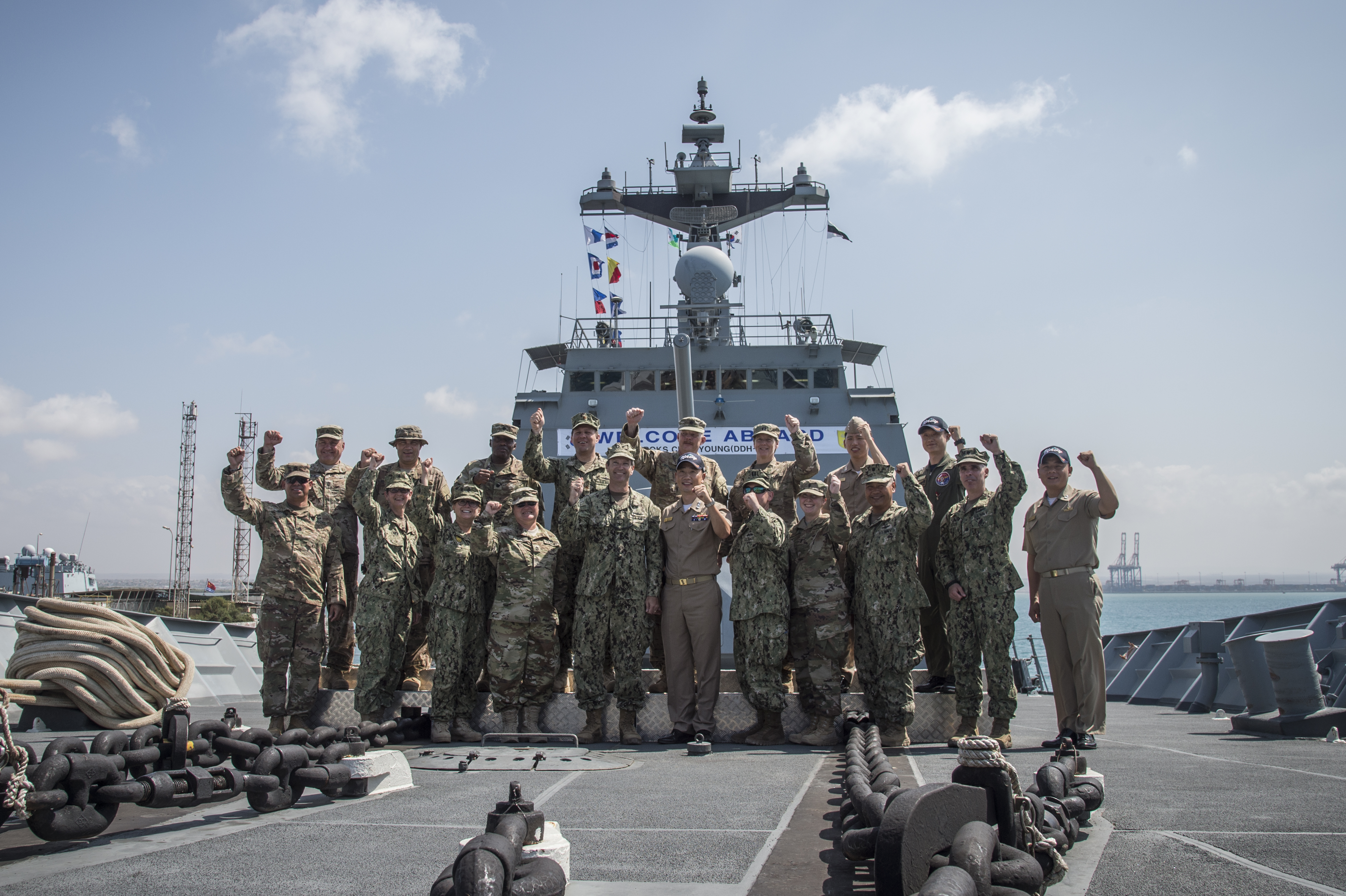 "Combined Joint Task Force-Horn of Africa joined members of Camp Lemonnier, Djibouti, pose for a group photo on the bow of the ROKS Choi Young DDH-981, May 8, 2017, a Chungmugong Yi Sun-sin-class destroyer in the South Korean navy. The group shouted a long-standing U.S.-Korea partnership mantra in unison, ""We go…together!,"" pumping a fist towards the sky. (U.S. Air National Guard photo by Tech. Sgt. Joe Harwood)"