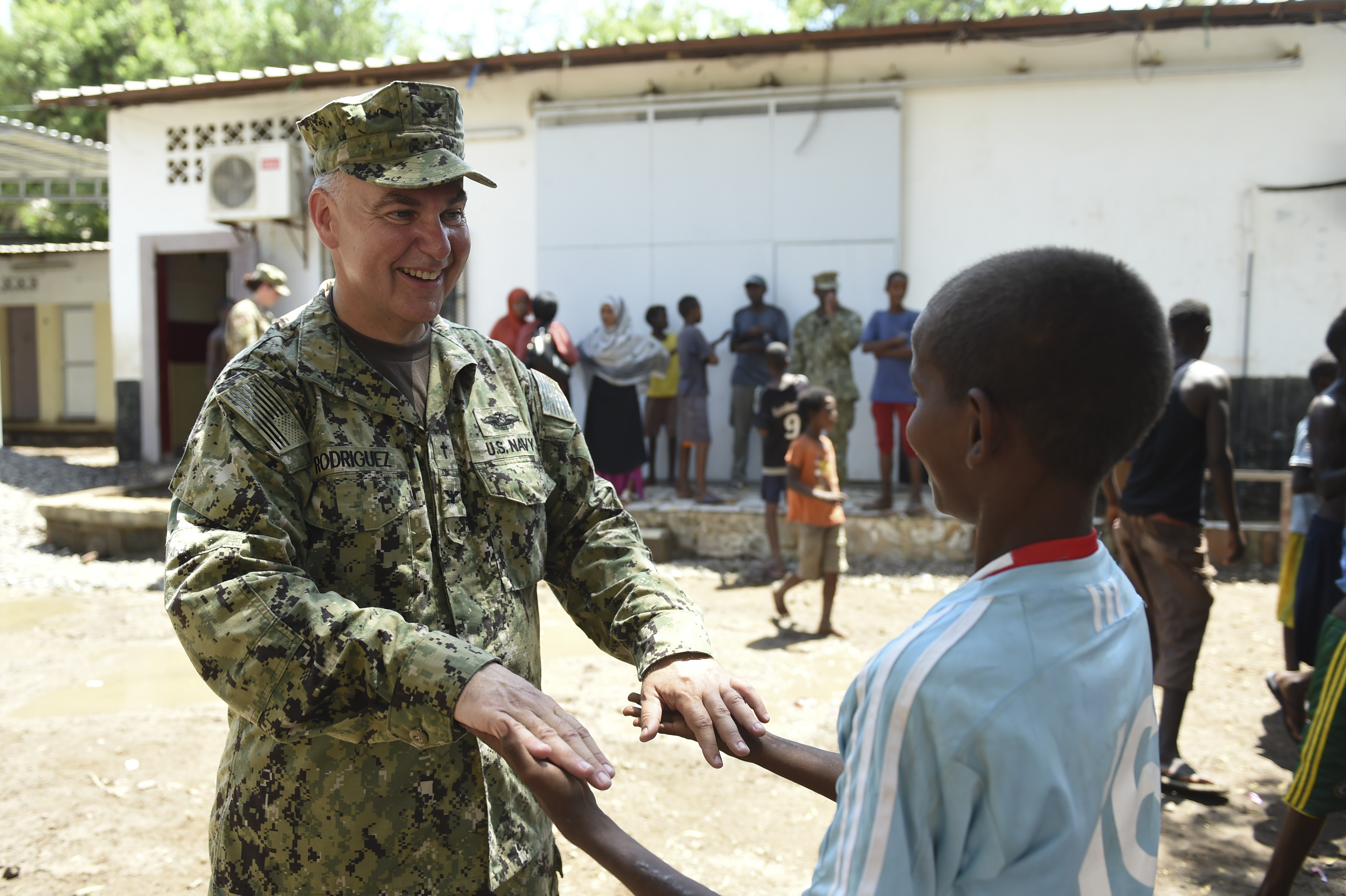U.S. Navy Capt. David Rodriguez, Combined Joint Task Force- Horn of Africa, Director of Religious Affairs plays a hand game with a child from Caritas Djibouti in downtown Djibouti, May 16, 2017. The Combined Joint Task Force - Horn of Africa Religious Affairs Office, organizes frequent trips to Caritas Djibouti as part of an ongoing effort to build sustainable partnerships throughout East Africa. (U.S. Air Force photo by Eboni Prince)