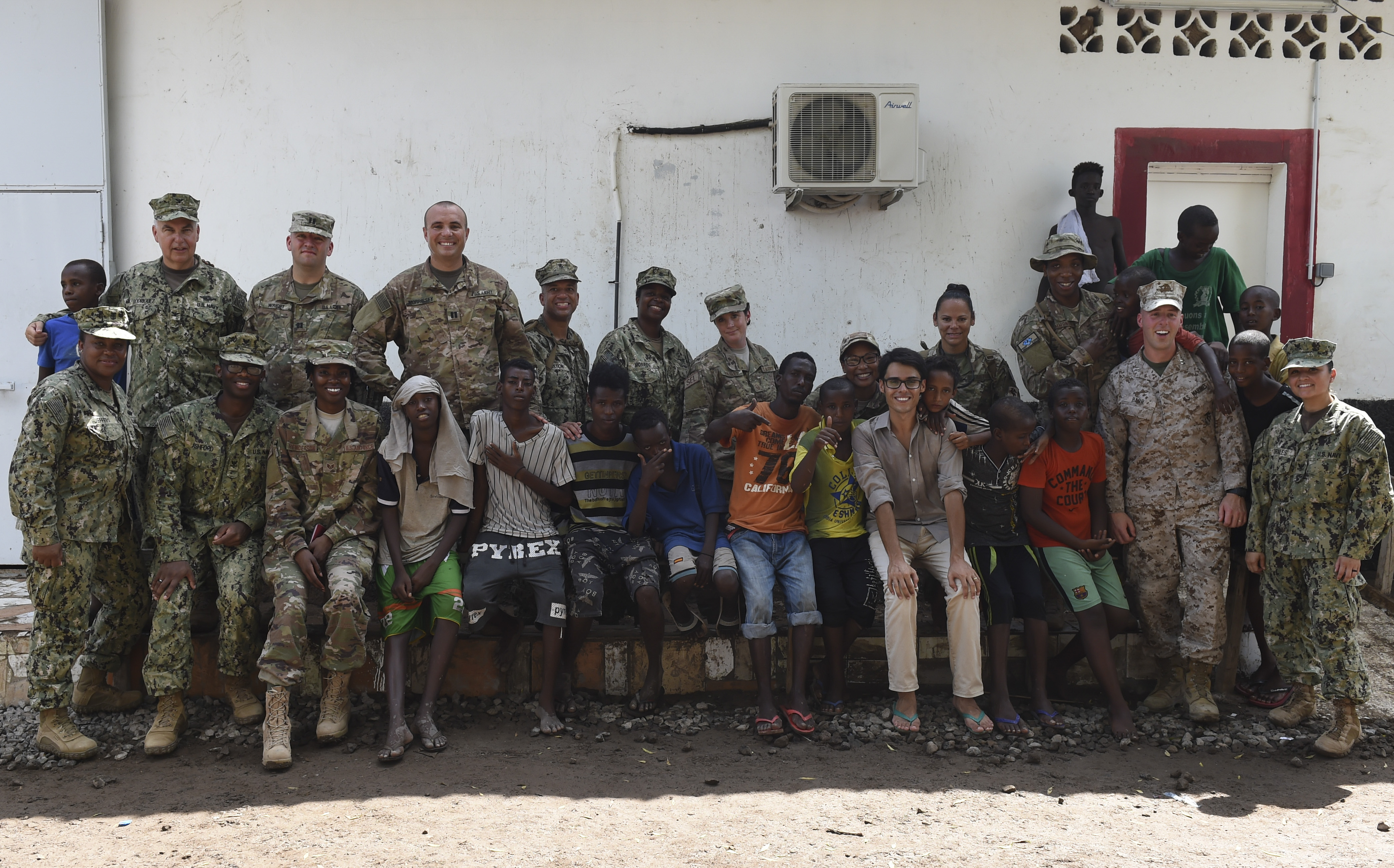 Children from Caritas Djibouti pose for a photo with service members from Camp Lemonnier, in downtown Djibouti, May 16, 2017. U.S. Service members assigned to the Combined joint Task Force - Horn of Africa, periodically visit with the mission to donate food items, toys, clothing and supplies. (U.S. Air Force photo by Eboni Prince)