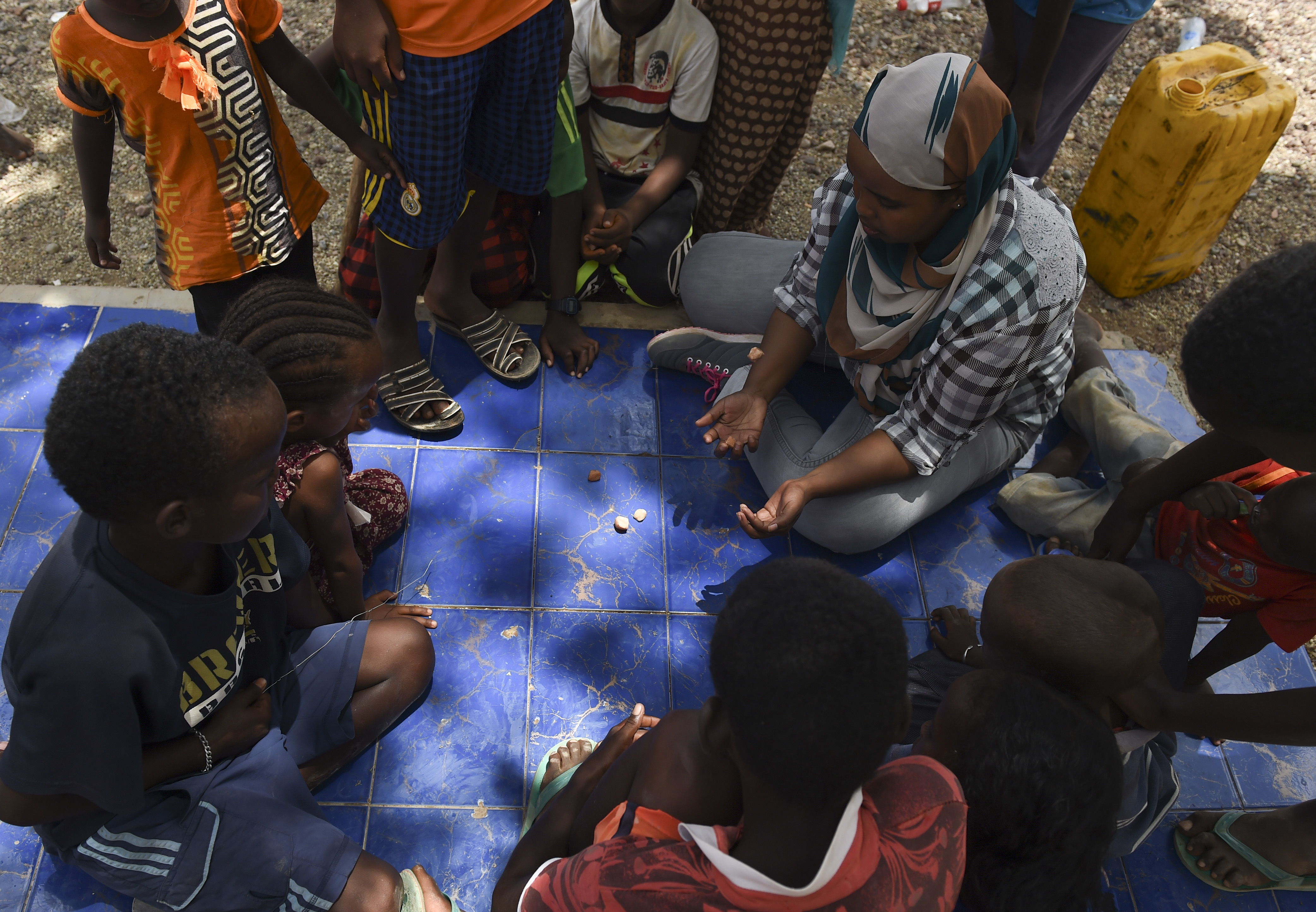 Fatouma Omar Guedi, a language interpreter, plays a game with several children in the village of Holhol, Djibouti, May 18, 2017. Language interpreters are essential to the success of civil affairs operations and act as liaisons between the military personnel and local key leaders in the east Africa region. (U.S. Air Force Photo by Eboni Prince)