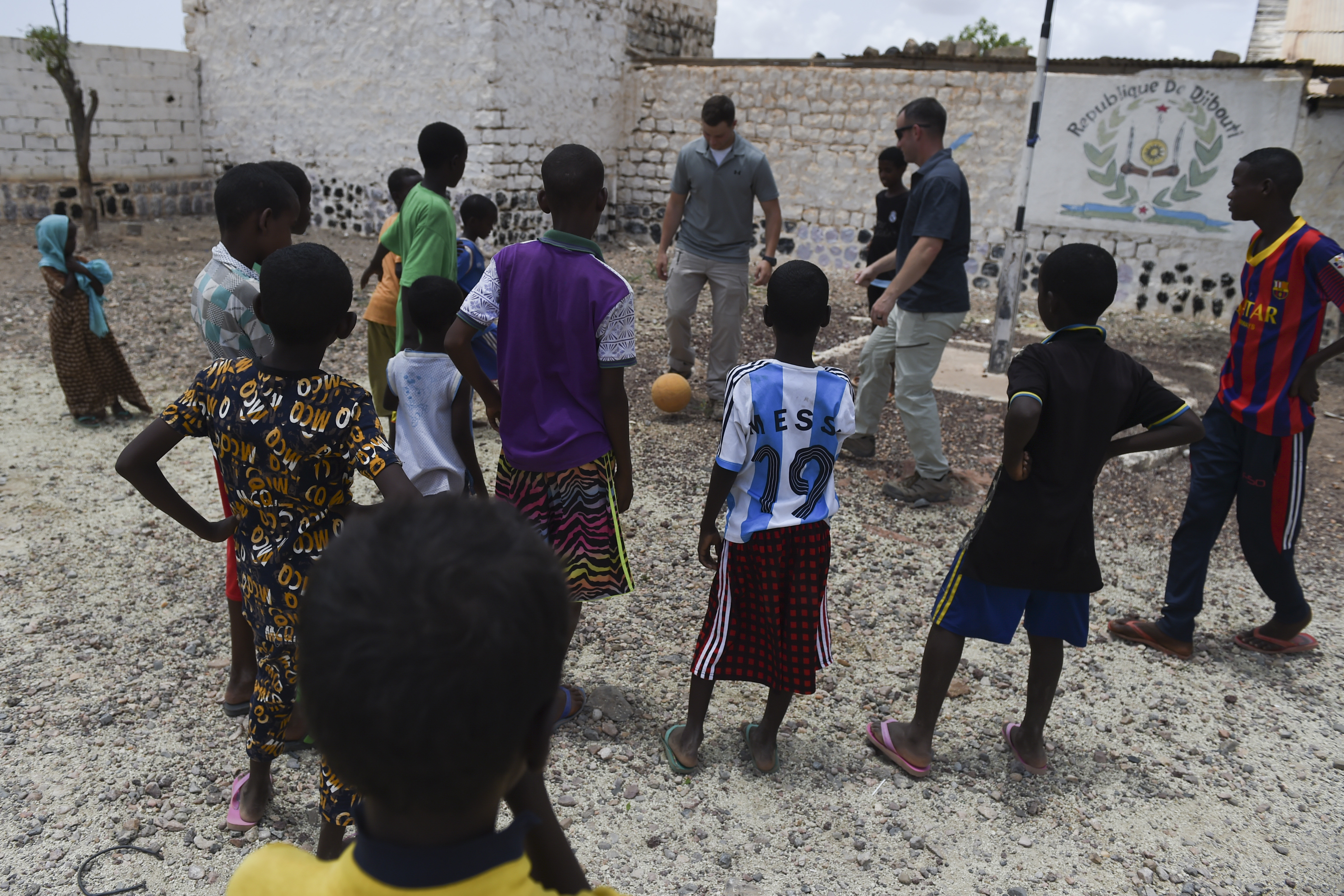 U.S. Army Sgt. Grady Kissee and Sgt. Robert Hawkins, both assigned to the Combined Joint Task Force-Horn of Africa, Military Information Support Operations, play soccer with children in the village of Holhol, Djibouti, May 18, 2017. Tactical Psychological Operations team members travelled with the 411th Civil Affairs Battalion, Bravo Company, Civil Affairs Team 3, to the village of Holhol to conduct a counter violent extremism assessment in support of the Combined Joint Task Force- Horn of Africa's effort to neutralize violent extremist organizations to create a stable, secure environment in East Africa. (U.S. Air Force Photo by Eboni Prince)