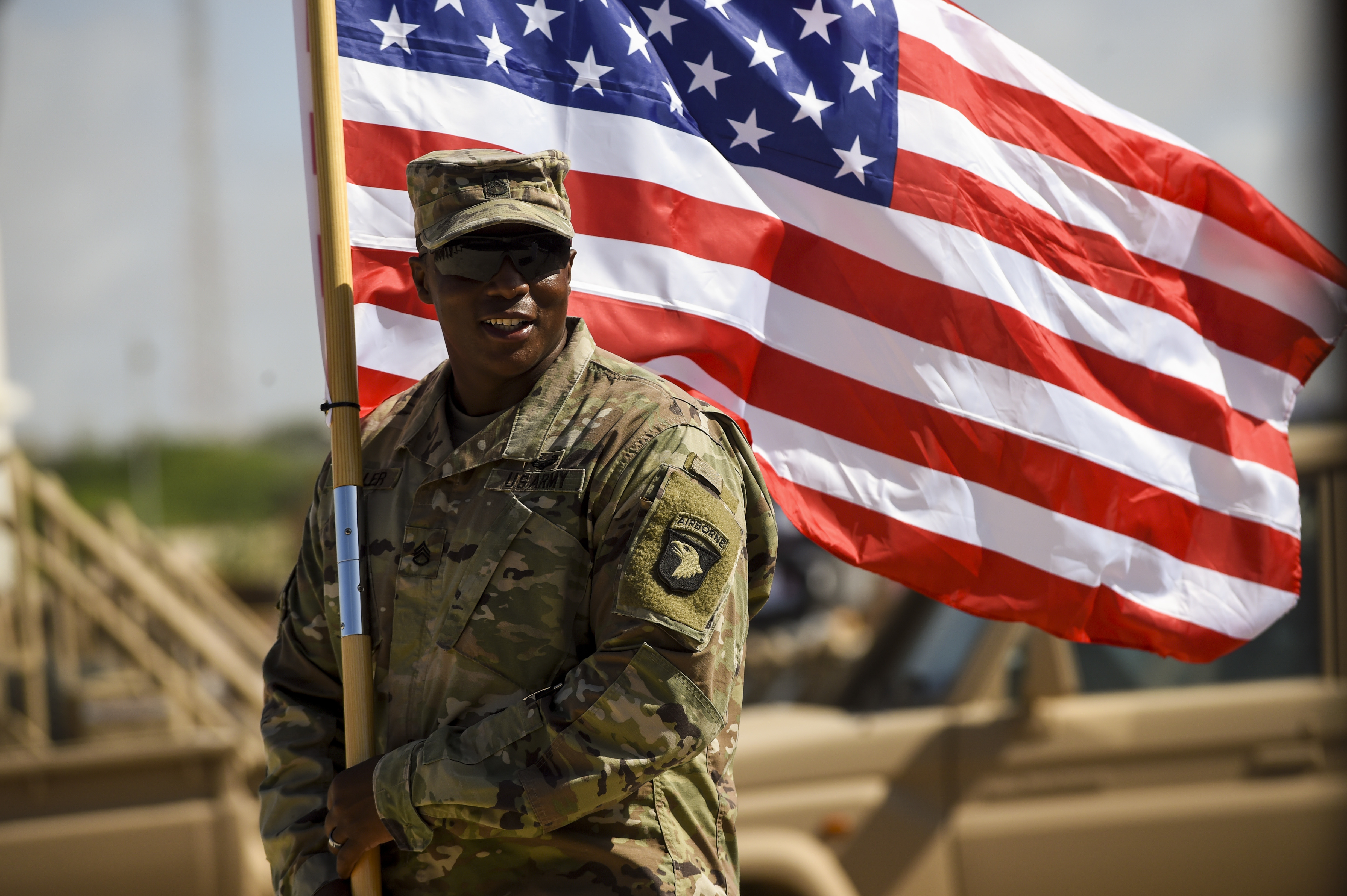 U.S. Army Staff Sgt. Anthony Miller with the 101st Airborne Division  holds the American flag during a graduation ceremony for Somali National Army soldiers May 24, 2017, in Mogadishu, Somalia. The logistics course focused on various aspects of moving personnel, equipment and supplies. (U.S. Air Force photo by Staff Sgt. Nicholas M. Byers)