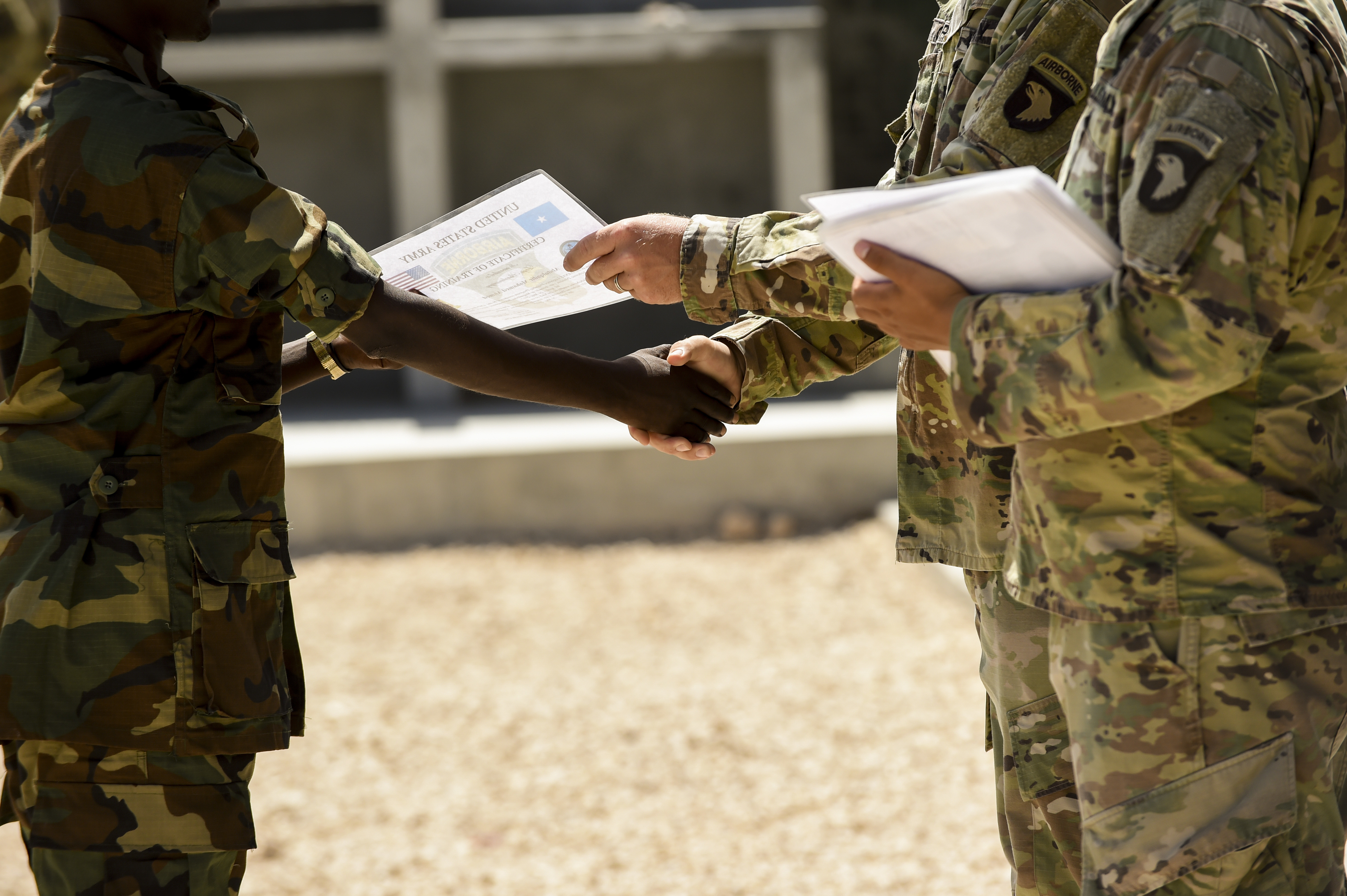 Soldiers from the U.S. Army's 101st Airborne Division present certificates of training completion to Somali National Army soldiers during a graduation ceremony May 24, 2017, in Mogadishu Somalia. The six-week course focused on various aspects of moving personnel, equipment and supplies. (U.S. Air Force photo by Staff Sgt. Nicholas M. Byers)