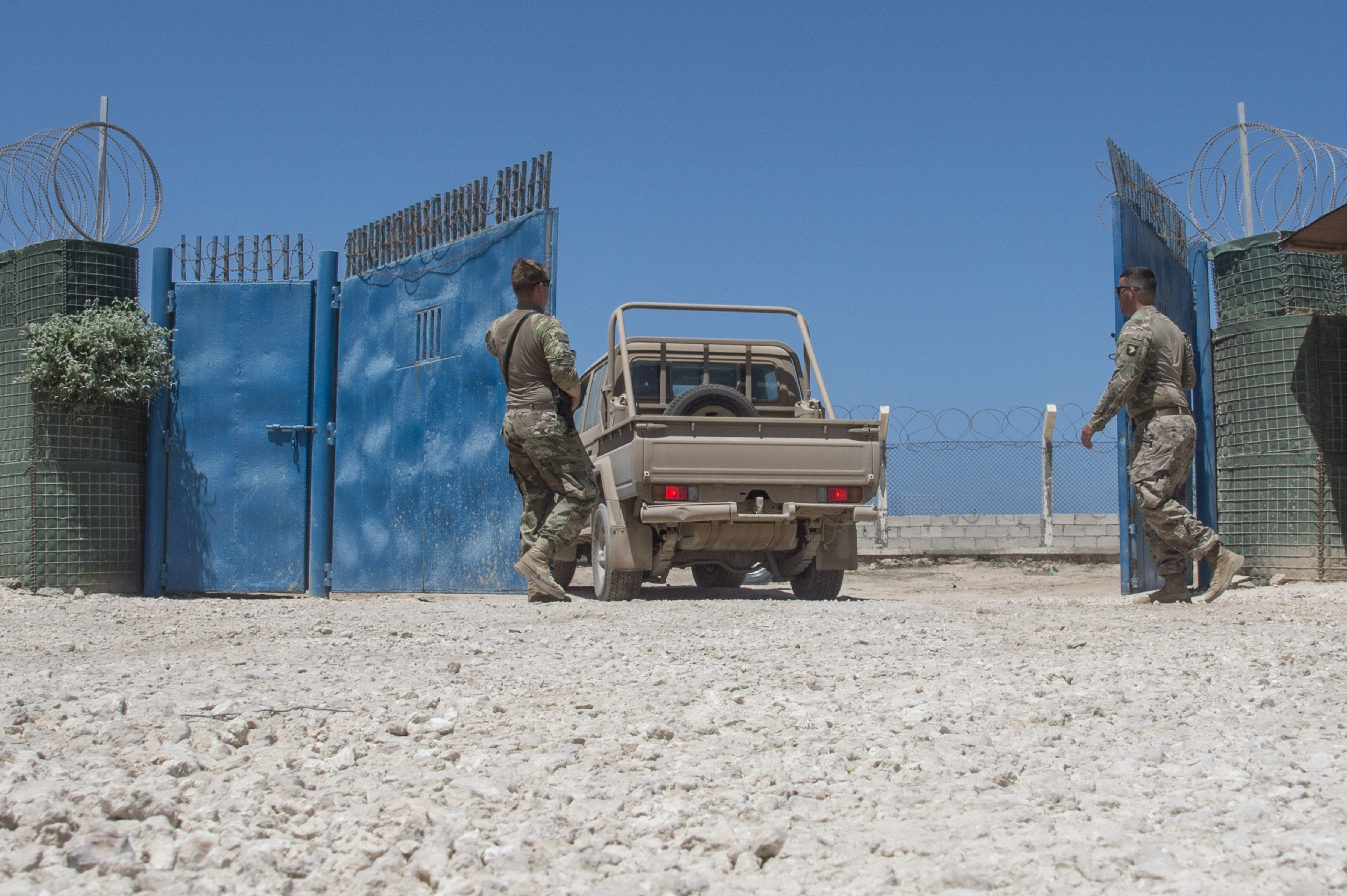U.S. Army Spc. Tyler Curtis and Spc. Blaine Grubb allow a Somali National Army (SNA) vehicle through the gate at a training site in Mogadishu, Somalia, on May 23, 2017, during a logistics course with the 101st Airborne Division from Fort Campbell, KY. These U.S. Soldiers, who belong to the 101st AD's 1st Brigade, 1st Battalion, Delta Company, 3rd Platoon, were tasked to secure the training site during a logistics training course for the SNA. The SNA's Danab battalion was the first to complete the logistics course, which concentrated on the organization of tactical movements of personnel, equipment and supplies. (U.S. Air National Guard photo by Tech. Sgt. Joe Harwood)