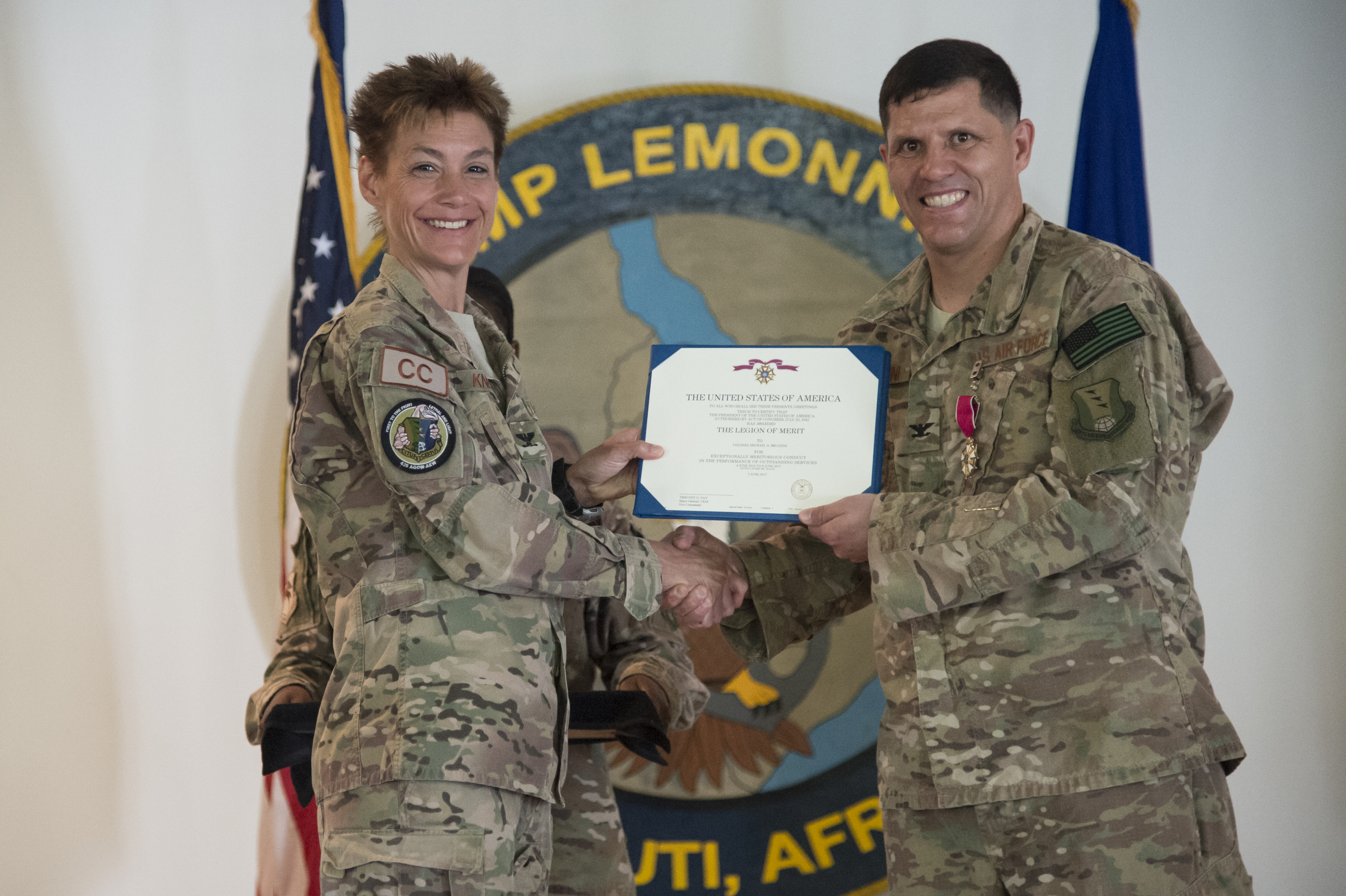 U.S. Air Force Col. Andra Kniep, 435th Air Expeditionary Wing commander, presents U.S. Air Force Col. Michael Bruzzini the Legion of Merit during the 449th AEG Change of Command ceremony June 9, 2017, at Camp Lemonnier, Djibouti. Cochran is relieving U.S. Air Force Col. Michael Bruzzini who has served as the 449th AEG Commander since June 6, 2016. The Legion of Merit is presented for exceptional meritorious conduct in the performance of outstanding services. (U.S. Air National Guard Photo by Tech. Sgt. Joe Harwood)