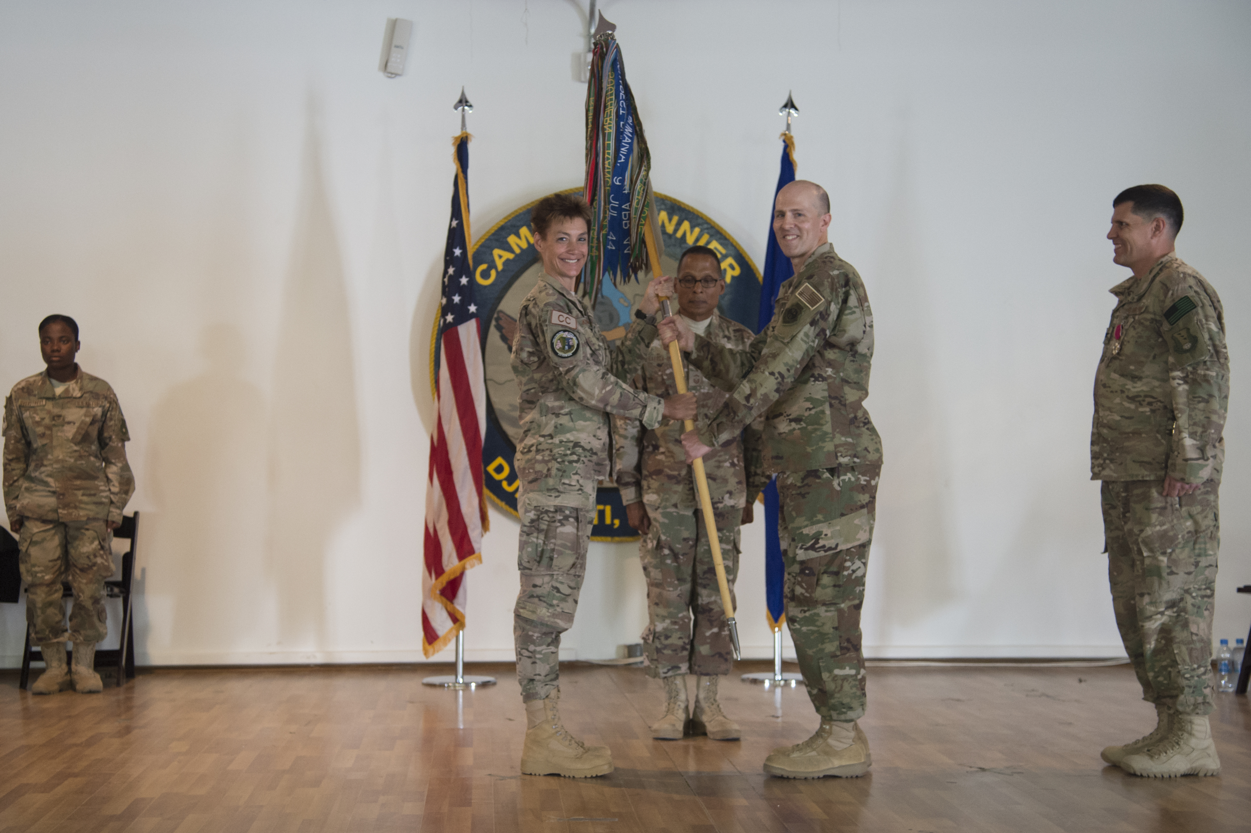 U.S. Air Force Col. Shawn Cochran, 449th Air Expeditionary Group incoming commander, receives the 449th AEG flag from U.S. Air Force Col. Andra Kniep, 435th Air Expeditionary Wing commander, during the 449th AEG Change of Command ceremony June 9, 2017, at Camp Lemonnier, Djibouti. Cochran is relieving U.S. Air Force Col. Michael Bruzzini who has served as the 449th AEG Commander since June 6, 2016. The passing of the flag is a military tradition signifying the change of authority and responsibility of a unit from one commander to another. (U.S. Air National Guard Photo by Tech. Sgt. Joe Harwood)