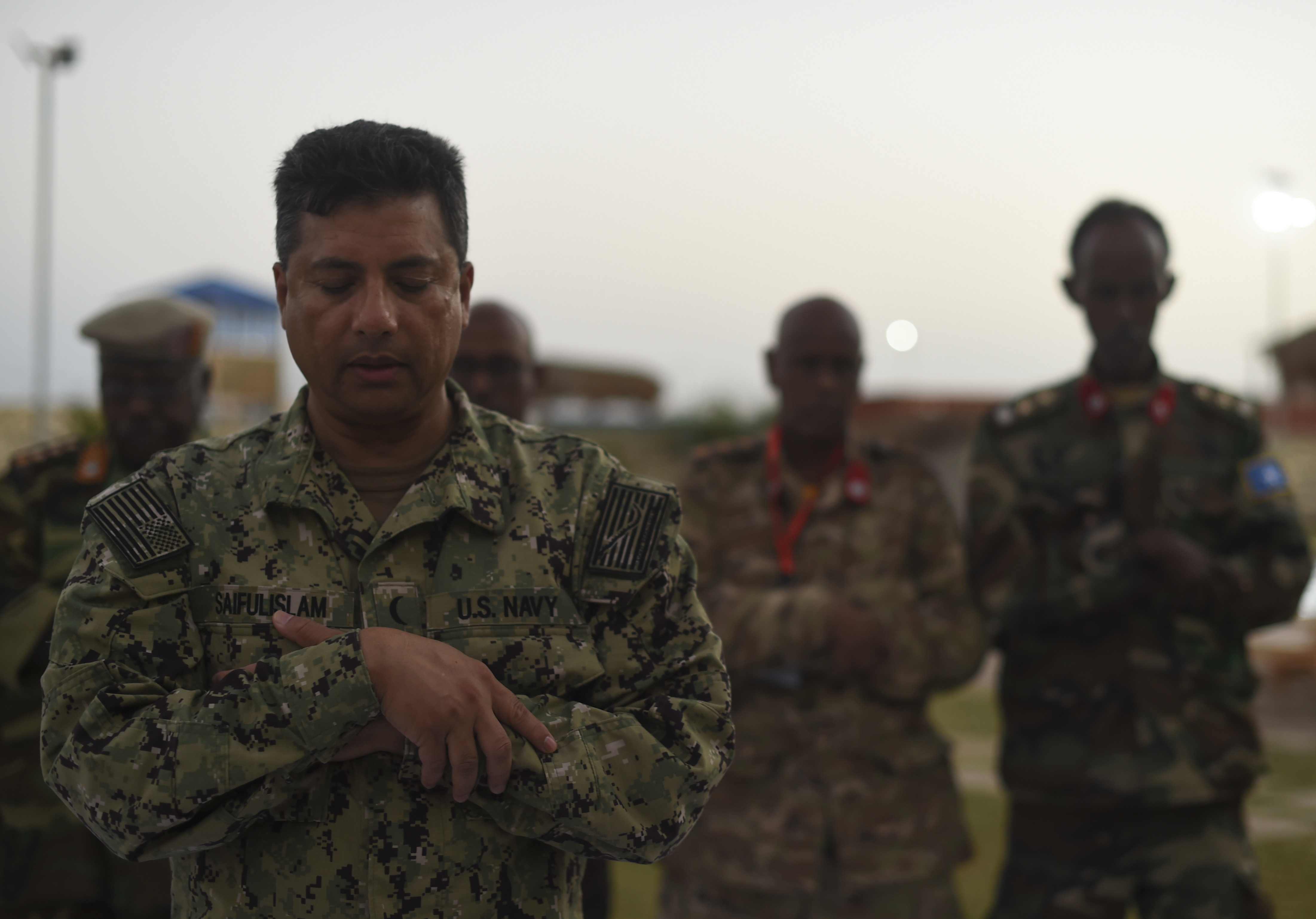 U.S. Navy Cmdr. Abuhena Saifulislam, U.S. Africa Command deputy command chaplain, leads a prayer before an Iftar with members of the Somali National Army at the Mogadishu International Airport, Mogadishu, Somalia, June 5, 2017. This was the first Iftar held between U.S. and SNA military personnel. Additionally, it was the first led by a U.S. Imam, who is a leader in the Islamic faith. (U.S. Air Force Photo by Staff Sgt. Eboni Prince)