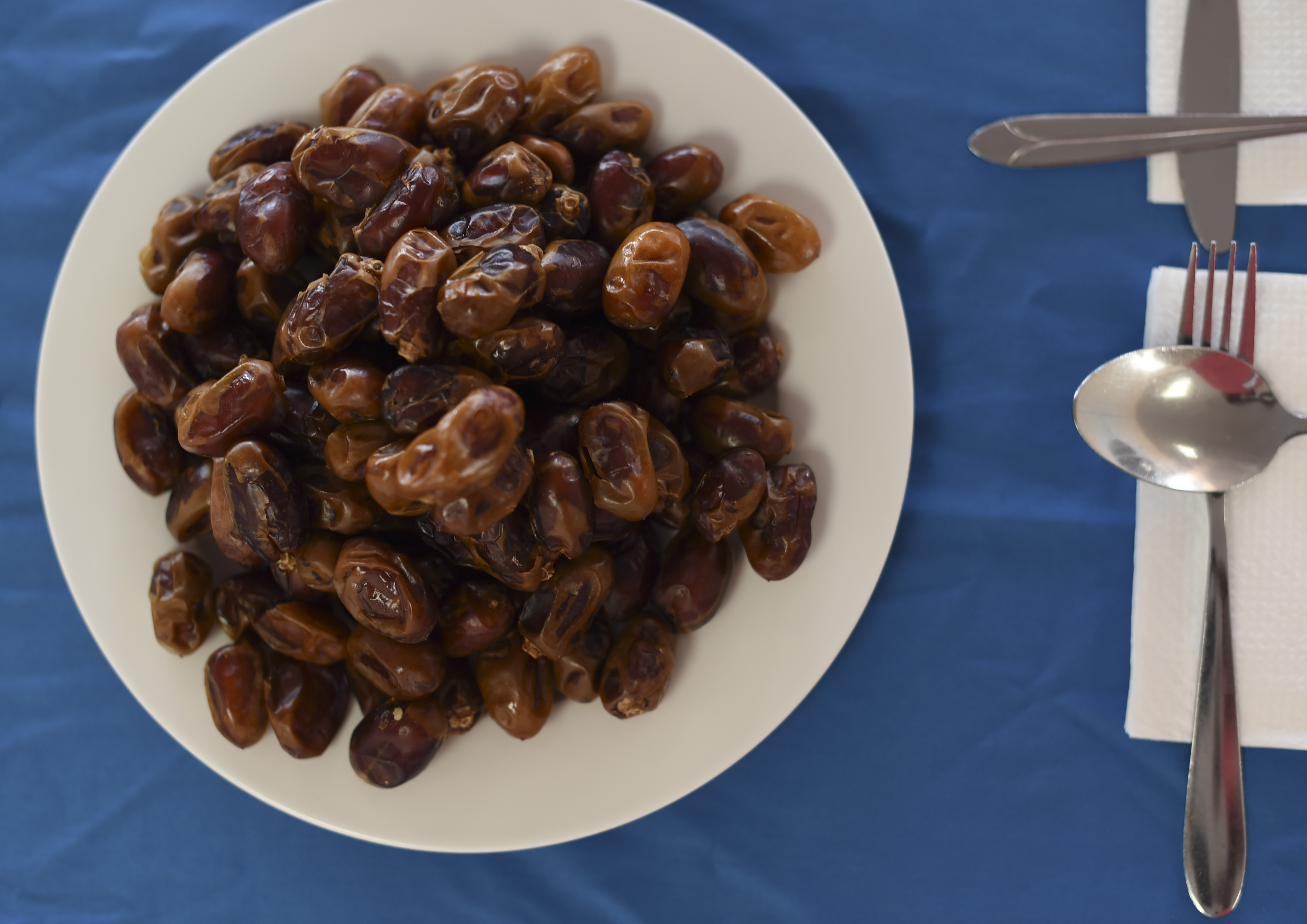 A plate of dates rests on a table before an Iftar held in Mogadishu, Somalia, June 5, 2017. During Ramadan, Muslims abstain from food and drink, including water from dawn till dusk. After sunset, eating dates and drinking water traditionally breaks the fast. (U.S. Air Force Photo by Staff Sgt. Eboni Prince)