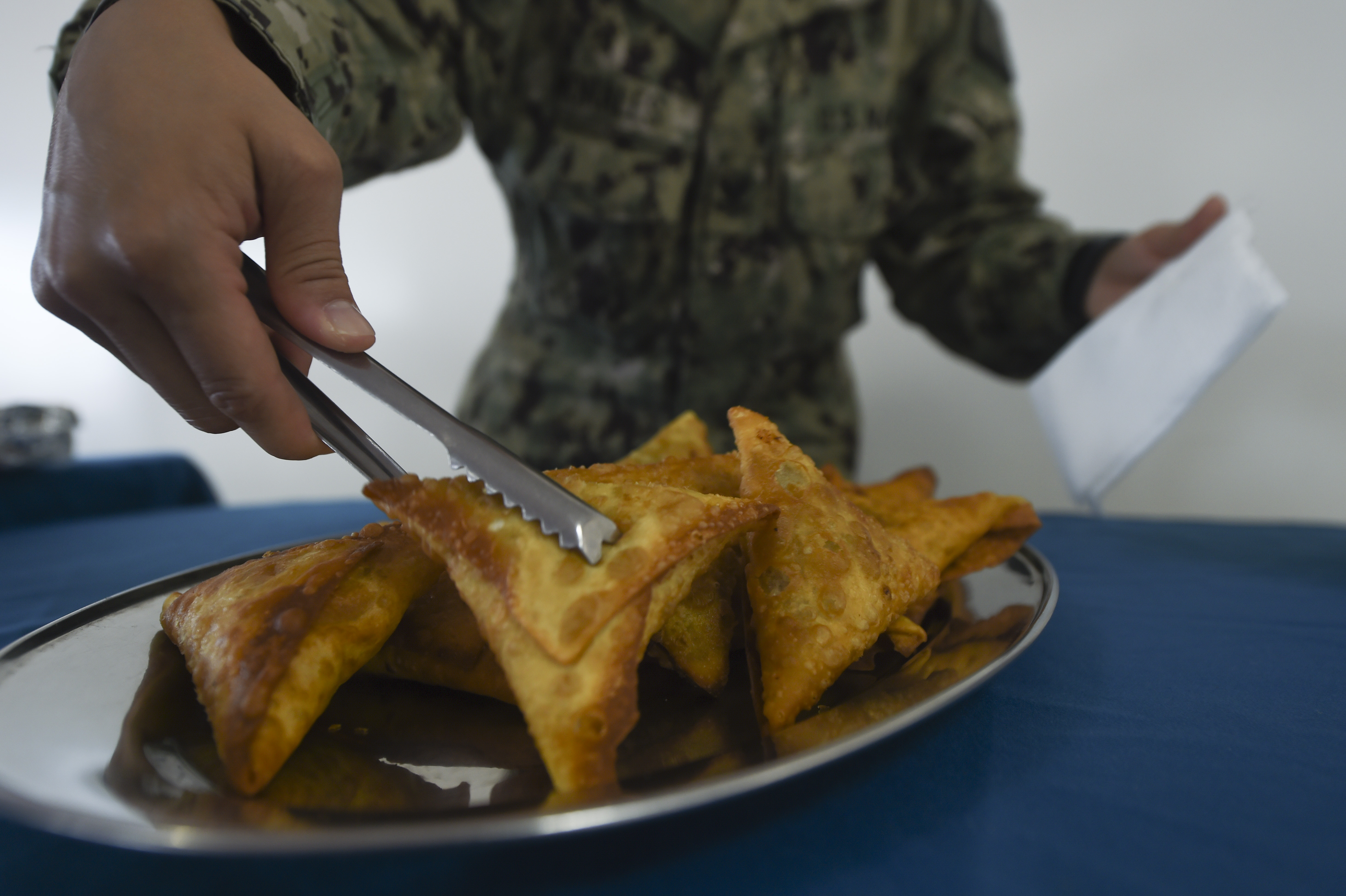 U.S. Navy Petty Officer 2nd Class Jocelyn Morales, Combined Joint Task Force – Horn of Africa religious affairs chaplain assistant, prepares a plate of samosas for a dual-service Iftar at the Mogadishu International Airport in Mogadishu, Somalia, June 5, 2017. Iftar is the evening meal when Muslims end their daily Ramadan fast at sunset.(U.S. Air Force photo by Staff Sgt. Eboni Prince)