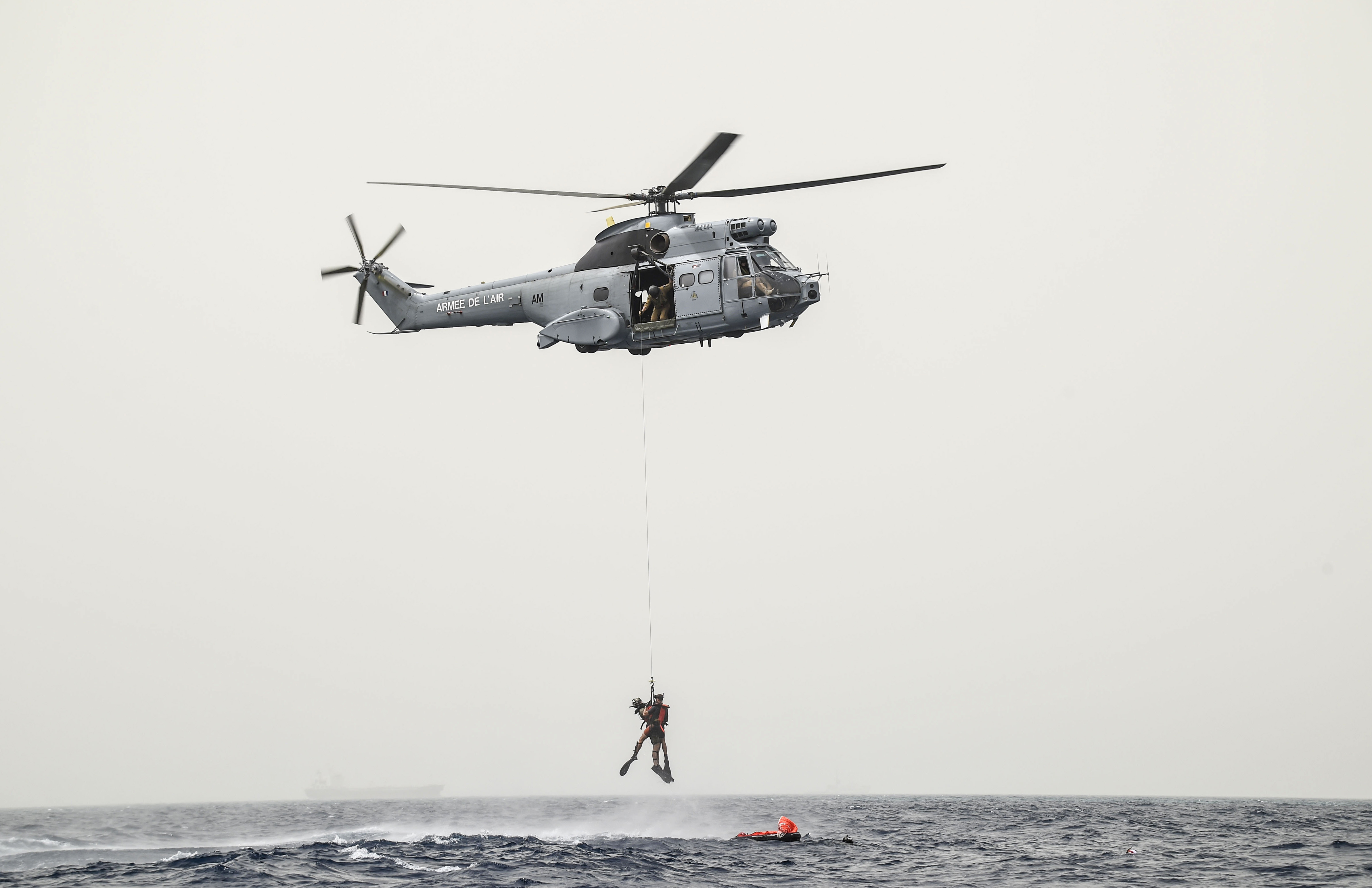 A French Air Force member assigned to the Transport Squadron ET 88 and a U.S. Air Force pararescueman from the 82nd Expeditionary Rescue Squadron, assigned to Combined Joint Task Force-Horn of Africa, are hoisted by a cable to a French Air Force Aérospatiale SA 330 Puma helicopter during a bilateral water operations exercise, in the Gulf of Tadjoura, July 3, 2017. This exercise marked the first bilateral rotary wing water operations exercise between the 82 ERQS and French forces.   (U.S. Air Force photo by Staff Sgt. Eboni Prince)