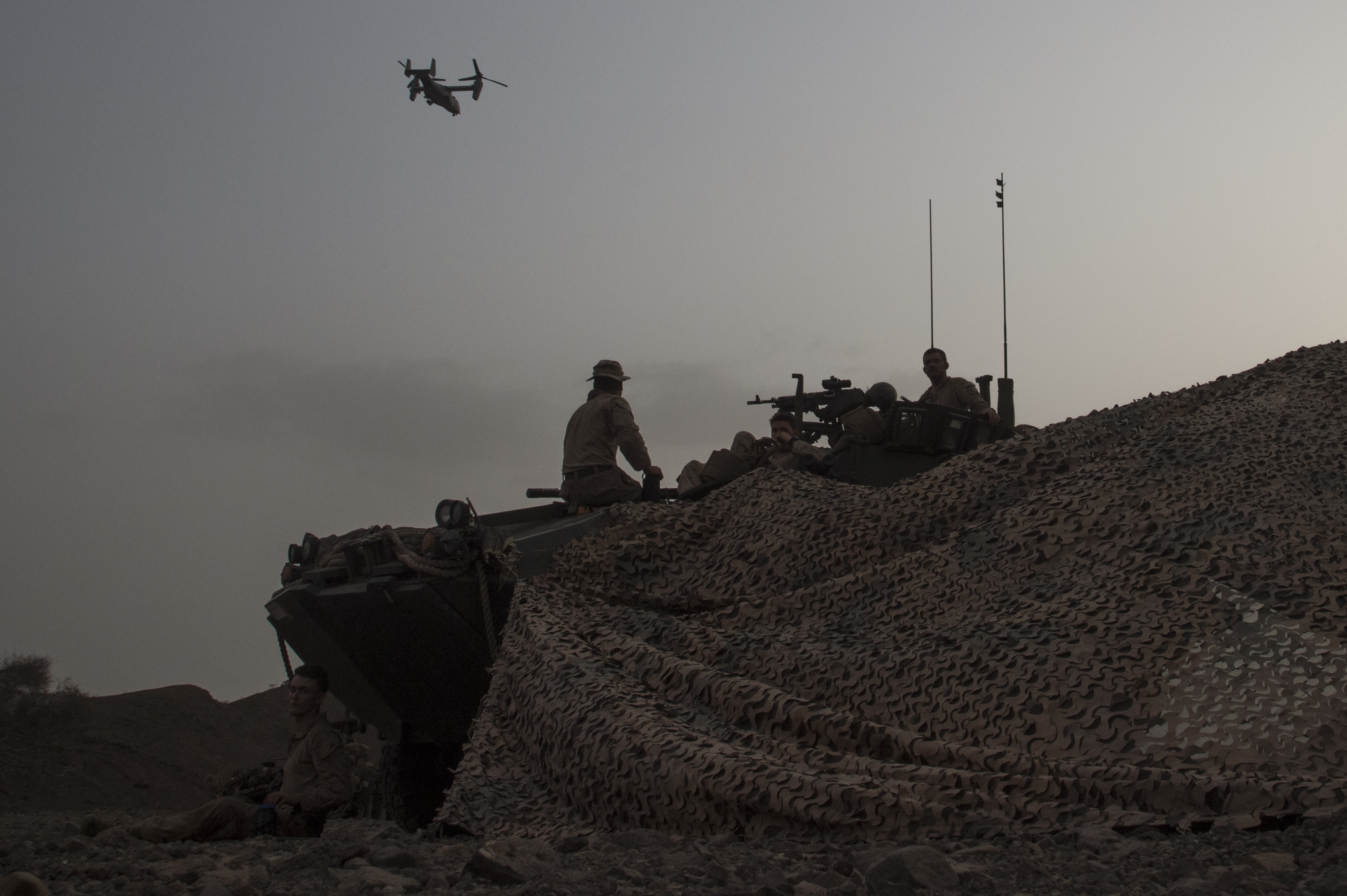 Marines with the 24th Marine Expeditionary Unit in an amphibious assault vehicle watch an MV-22 Osprey fly over during an exercise on the east coast of Africa from the amphibious assault ship USS Bataan (LHD 5) July 9, 2017. Marines with the 24th MEU conduct annual training while deployed with the Bataan Amphibious Ready Group to stay mission ready and maintain Marine Corps standards. Bataan and its ARG are deployed to the U.S. 5th Fleet area of operations in support of maritime security operations designed to reassure allies and partners and preserve the freedom of navigation and the free flow of commerce in the region. (U.S. Air National Guard photo by Tech. Sgt. Joe Harwood)