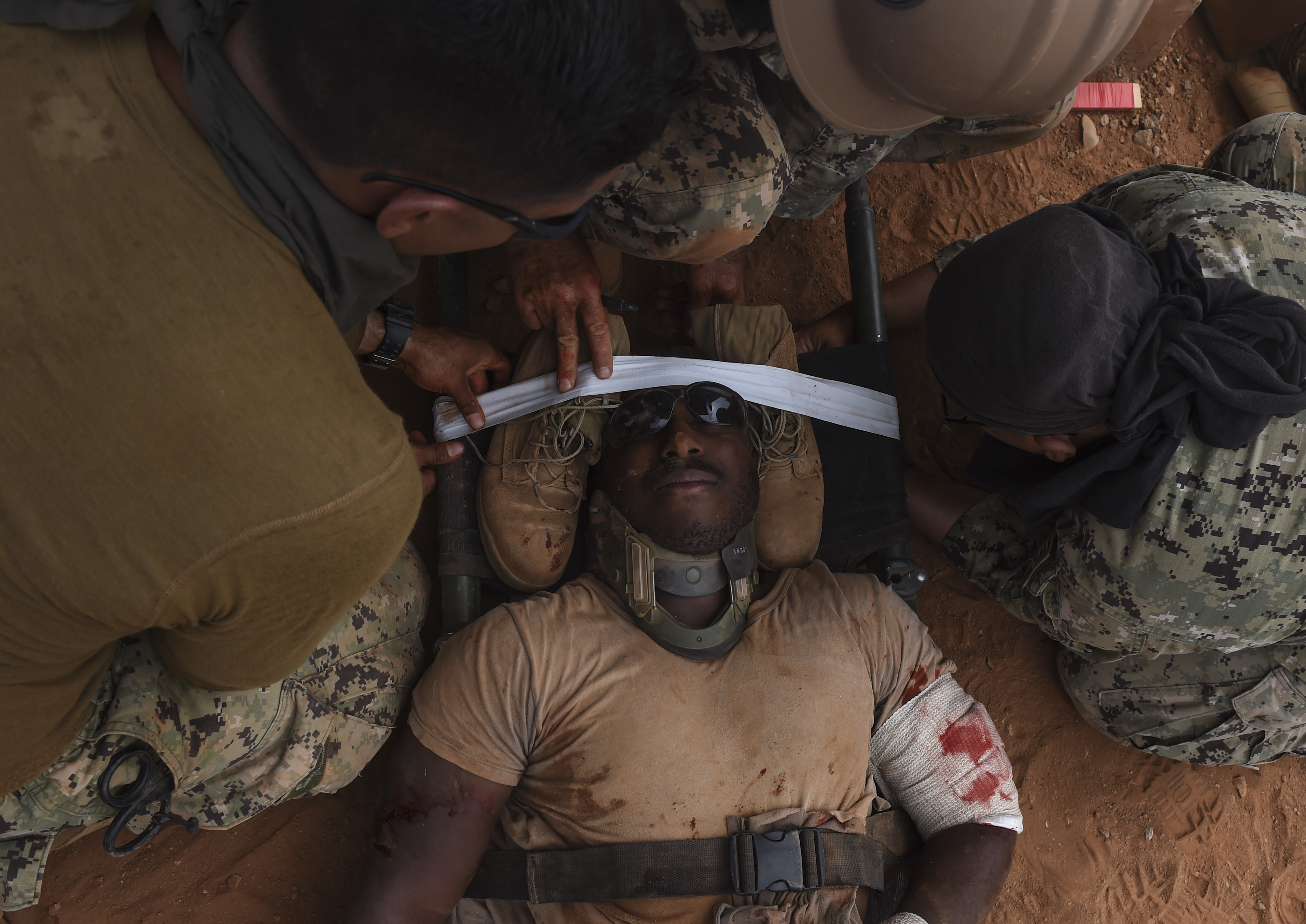 U.S. Navy Petty Officer 3rd Class Melvin Taylor from the Naval Mobile Construction Battalion One, a maneuver unit of the Combined Joint Task Force-Horn of Africa, receives care for his simulated injuries during a bilateral exercise with French forces in the Arta region, July 19, 2017. CJTF-HOA conducts exercises to maintain readiness and evaluate capability of U.S. and international forces, or to establish/maintain relationships and contribute to capacity building. (U.S. Air Force photo by Staff Sgt. Eboni Prince)