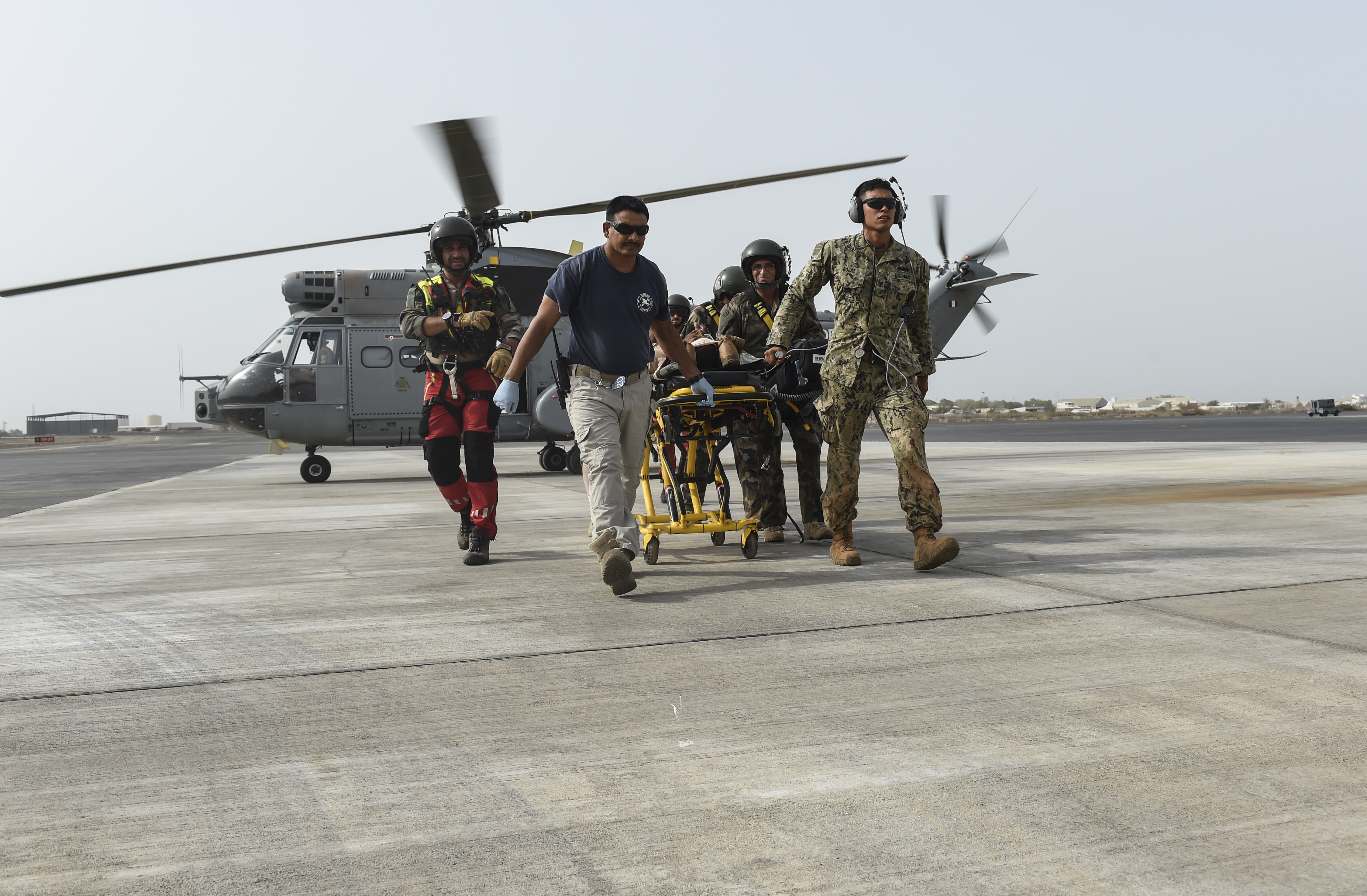 U.S. Navy Hospital Corpsman 3rd Class David Rojas from the Naval Mobile Construction Battalion One, a maneuver unit of the Combined Joint Task Force-Horn of Africa, along with emergency medical services personnel and members  of the French Air Force  Tactical Airlift Squadron 88, transport a patient from a SA 330 Puma helicopter across the flightline, during a bilateral exercise with French forces at Camp Lemonnier, July 20, 2017. CJTF-HOA partners with French counterparts to strengthen regional cooperation and interoperability, enhancing the mutual ability to conduct operations in the region. (U.S. Air Force photo by Staff Sgt. Eboni Prince)