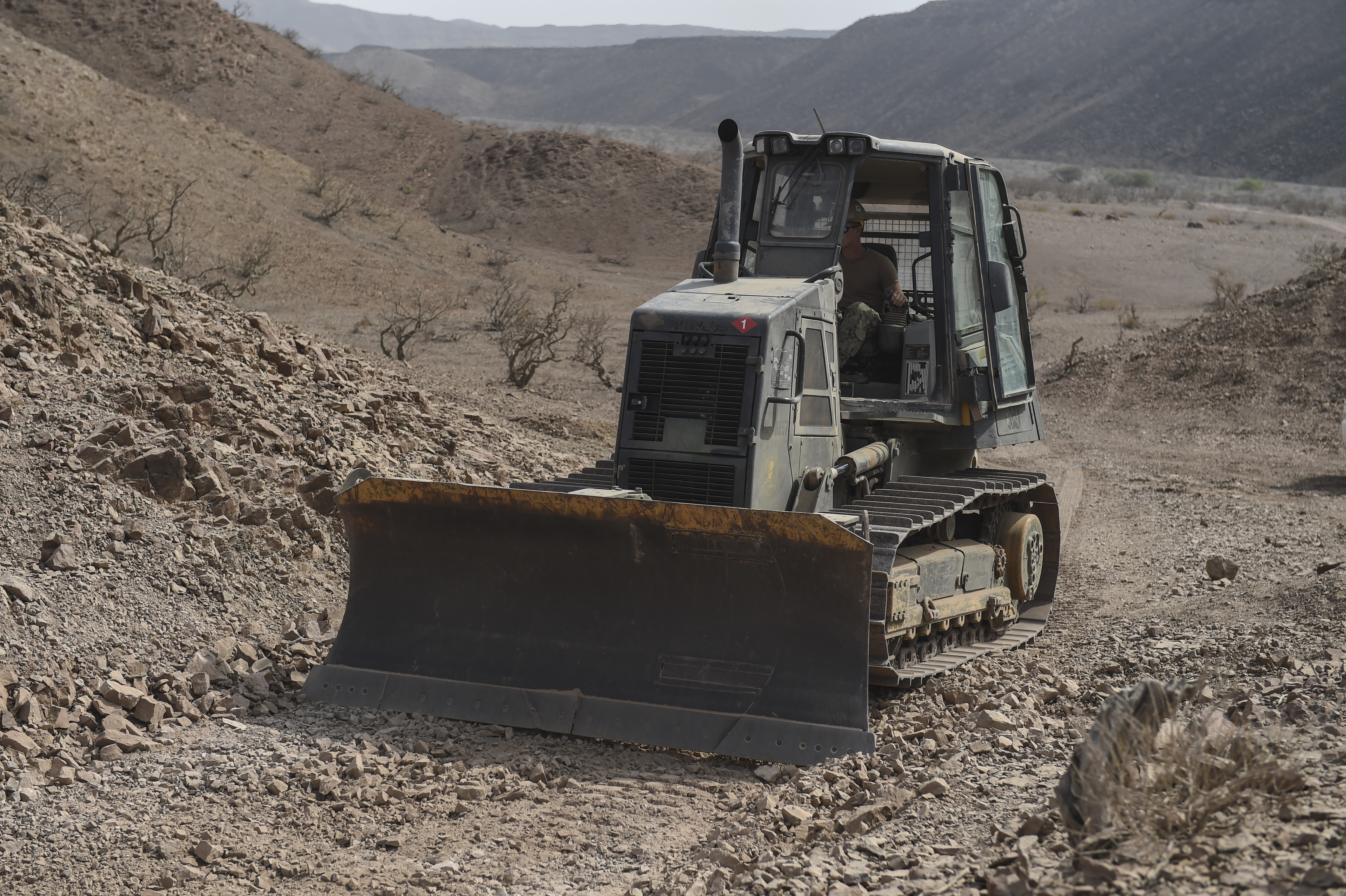 An equipment operator with the U.S. Naval Mobile Construction Battalion One uses a bulldozer to push rocks and dirt at a range near Arta, Djibouti, July 27, 2017. NMCB One supports Combined Joint Task Force-Horn of Africa through the completion of various construction projects throughout East Africa that aid in promoting stability in the region. (U.S. Air Force photo by Staff Sgt. Eboni Prince)