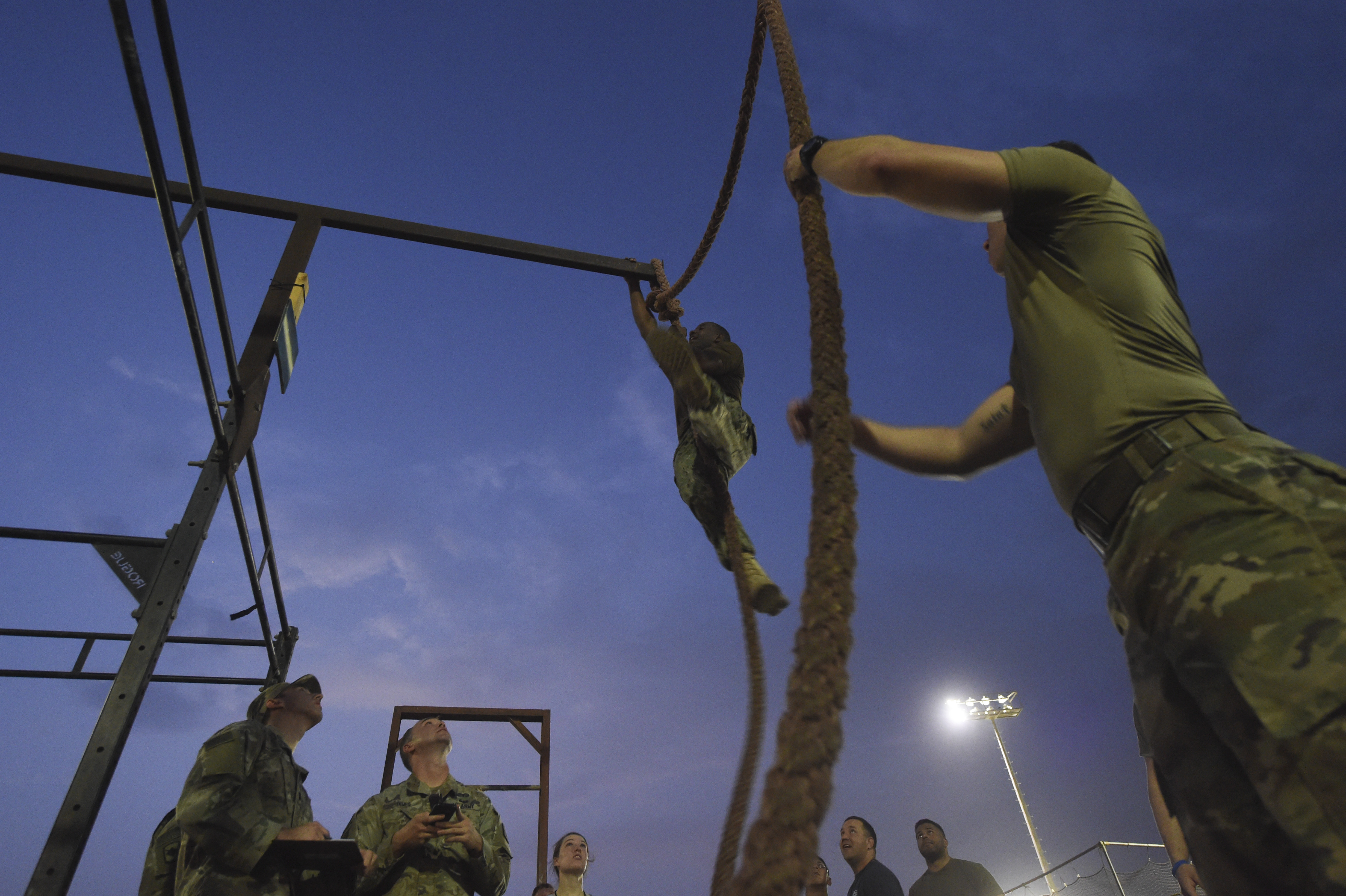 A U.S. service member completes a rope climb during a physical training test at Camp Lemonnier, Djibouti, Aug. 5, 2017. The test was in preparation for an upcoming multi-day French Desert Commando Course that will challenge participants physically and mentally through land and water obstacles, combat scenarios and extreme endurance exercises while surviving in austere field conditions. (U.S. Air Force photo by Staff Sgt. Eboni Prince)