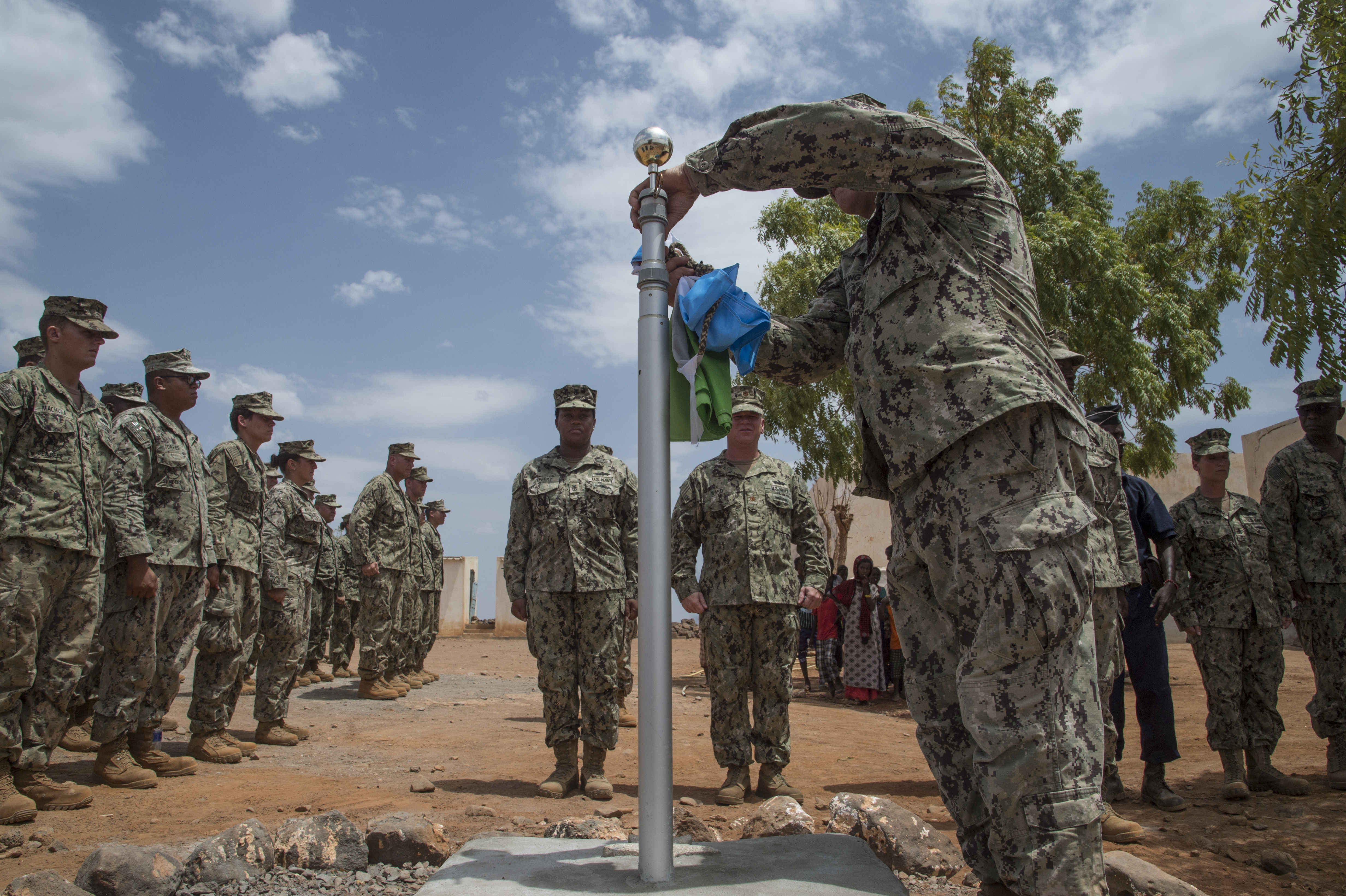 U.S. Navy Chief Petty Officer John Young of Naval Mobile Construction Battalion ONE raises the Djiboutian flag dedicated to the local village Chief Hassan Diama as Seabees assigned to Combined Joint Task Force-Horn of Africa gather for the flag ceremony at a remote village in the Arta region of Djibouti, Aug. 17, 2017. The flag-raising ceremony represented the enduring relationships created as the NMCB 1 worked to build a clinic complex there. NMCB 133 has replaced NMCB 1 and will continue working on the project. (U.S. Air National Guard photo by Tech. Sgt. Joseph Harwood)
