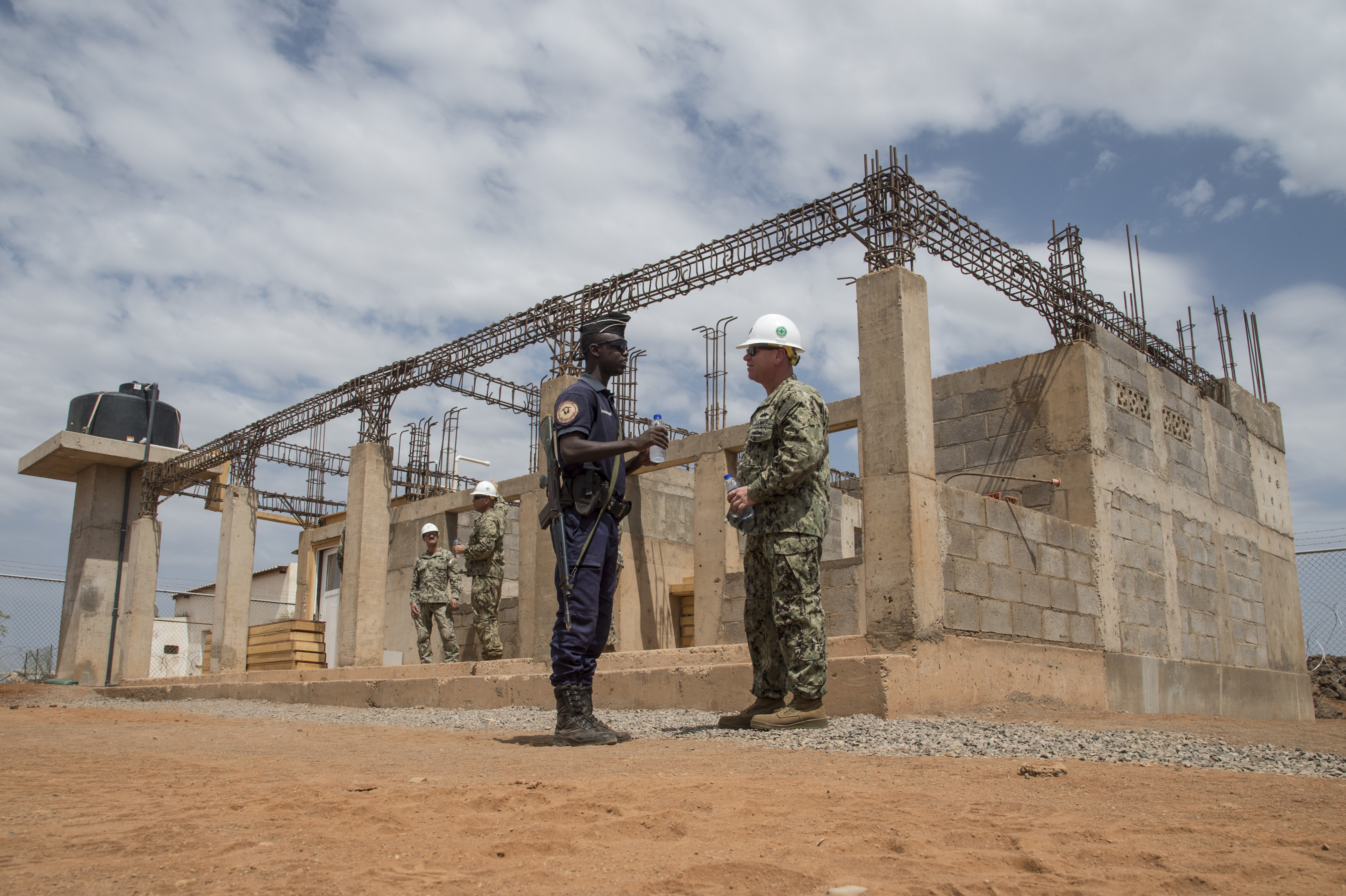 Lt. Cdr. Jason Ward, Commander of Naval Mobile Construction Battalion ONE (NMCB 1) assigned to Combined Joint Task Force-Horn of Africa speaks with the Djiboutian Gendarmerie securing the construction site at Ali Oune, Djibouti, where they are building a medical center, Aug. 17, 2017. The project was started by NMCB 1 and is being relieved by NMCB 133 who will continue working on the project. (U.S. Air National Guard photo by Tech. Sgt. Joe Harwood)