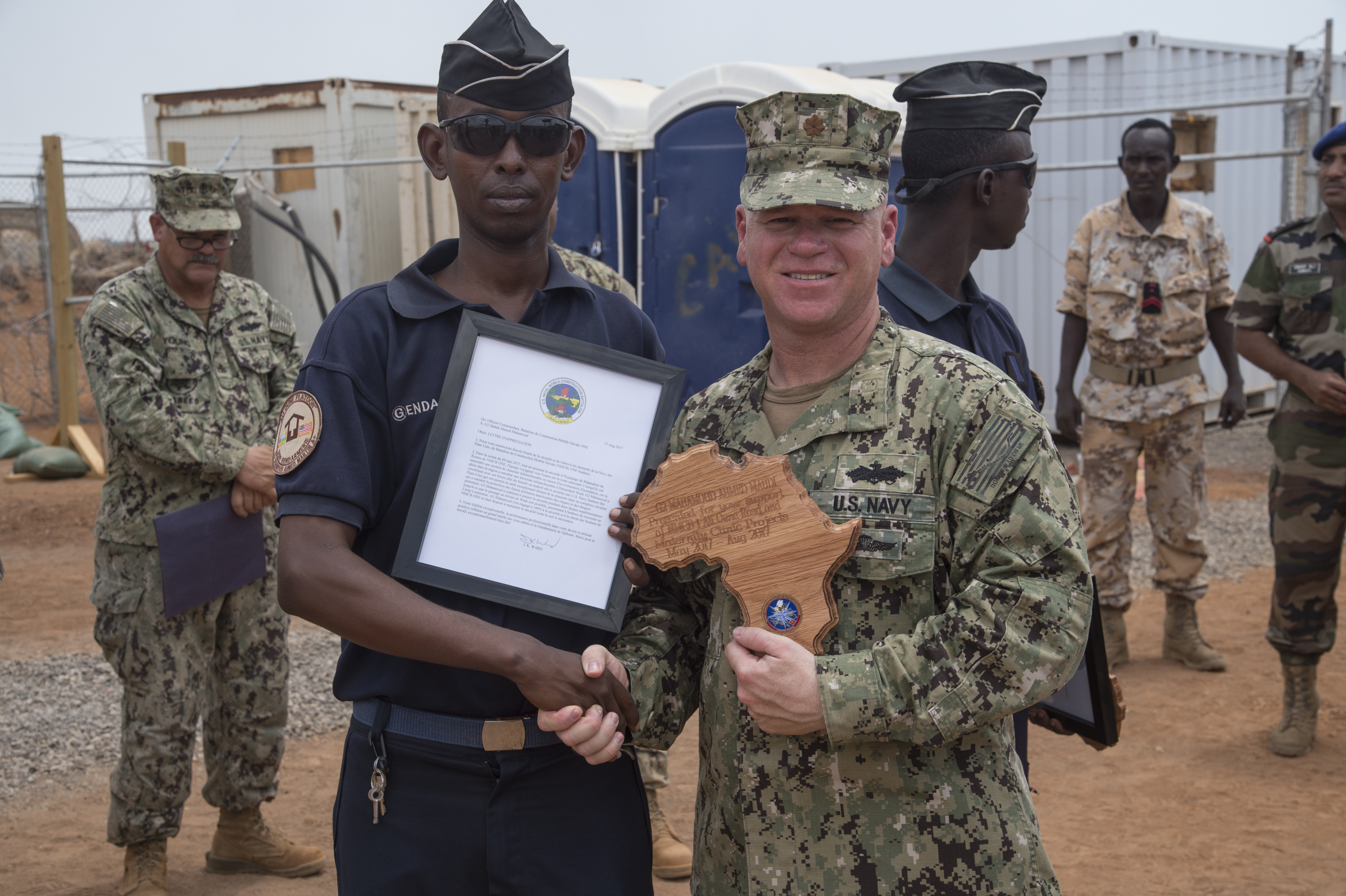 Naval Mobile Construction Battalion ONE officer-in-charge U.S. Navy Lt. Cmdr. Jason Ward recognizes Djiboutian Gendarmerie Mahamoud Ahmed Mahdi for providing additional security to the Seabees assigned to Combined Joint Task Force-Horn of Africa while they worked on a construction site at a remote village in the Arta region of Djibouti, Aug. 17, 2017. The project was started by NMCB 1, now replaced by NMCB 133, who will continue working on the project. (U.S. Air National Guard photo by Tech. Sgt. Joseph Harwood)