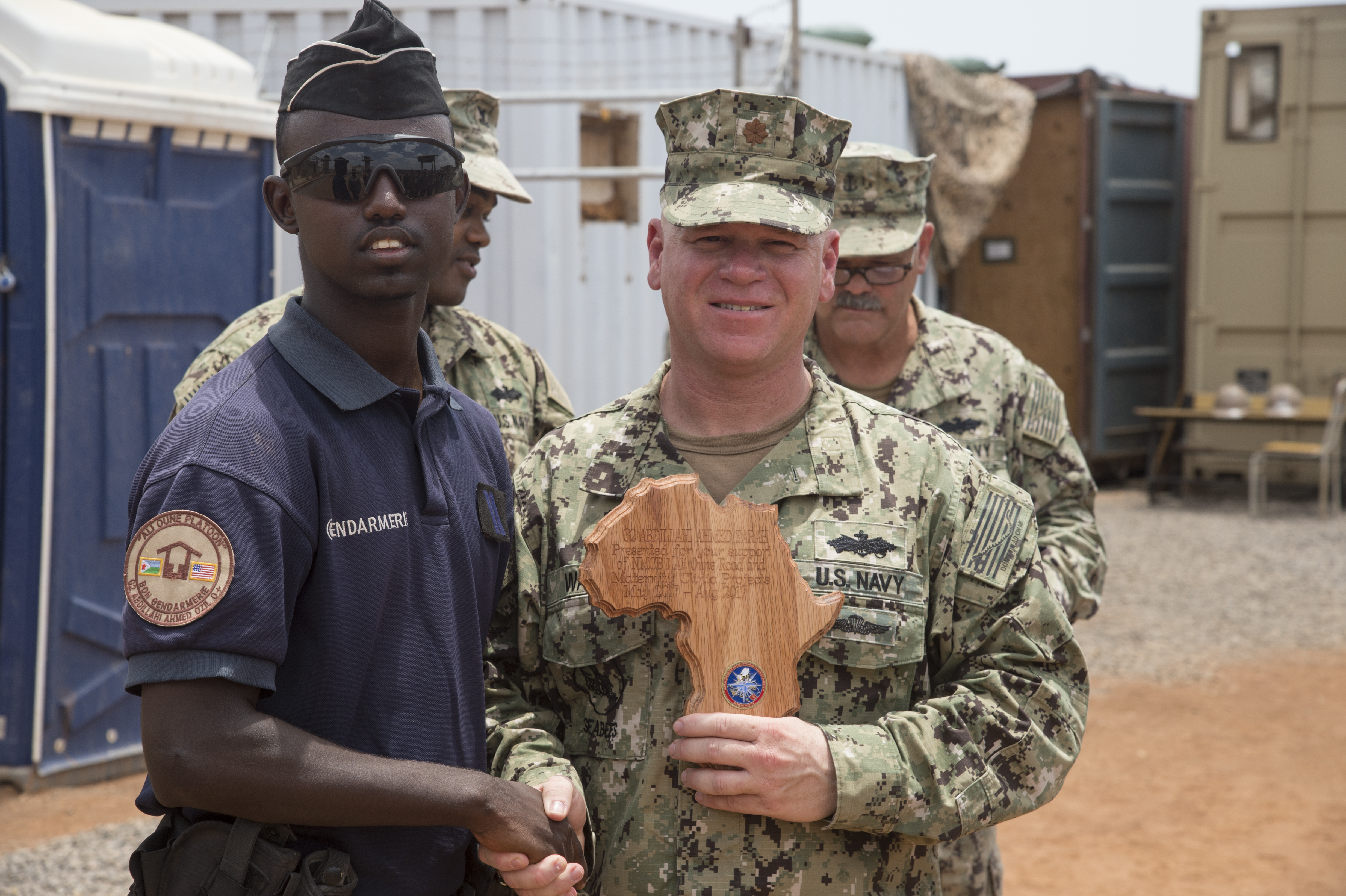 Naval Mobile Construction Battalion ONE officer-in-charge U.S. Navy Lt. Cmdr. Jason Ward recognizes Djiboutian Gendarmerie Abdillahi Ahmed Farah for securing Seabees assigned to Combined Joint Task Force-Horn of Africa while they worked on a construction site at a remote village in the Arta region of Djibouti, Aug.  17, 2017. The project was started by NMCB 1, now replaced by NMCB 133, who will continue working on the project. (U.S. Air National Guard photo by Tech. Sgt. Joseph Harwood)