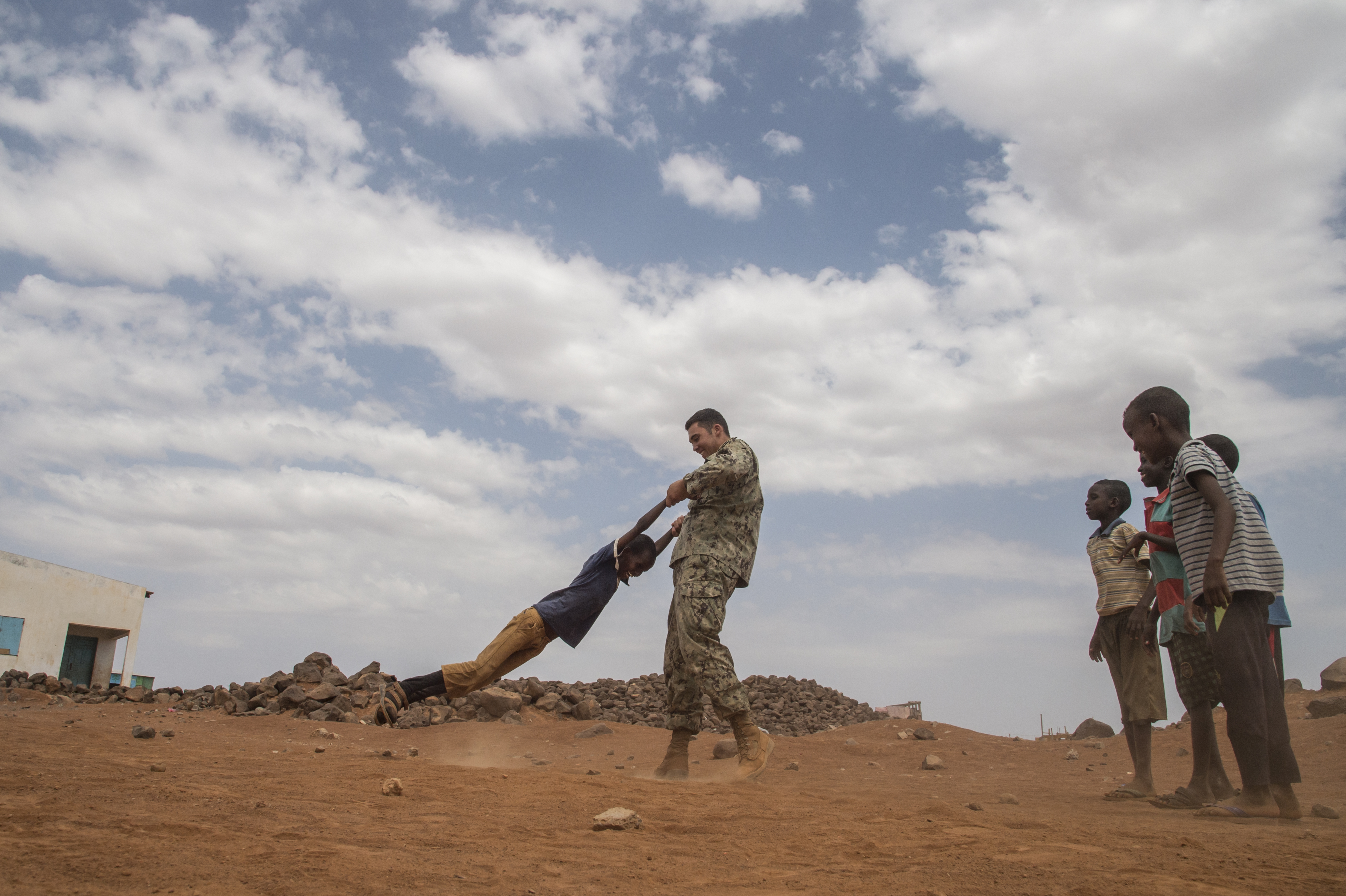 U.S. Navy Seabee Seaman Jesse Martinez, assigned to Combined Joint Task Force-Horn of Africa, plays with local children on a construction site at a remote village in the Arta region of Djibouti, Aug. 17, 2017. The project was started by Naval Mobile Construction Battalion ONE, now replaced by NMCB 133, who will continue working on the project. (U.S. Air National Guard photo by Tech. Sgt. Joseph Harwood)