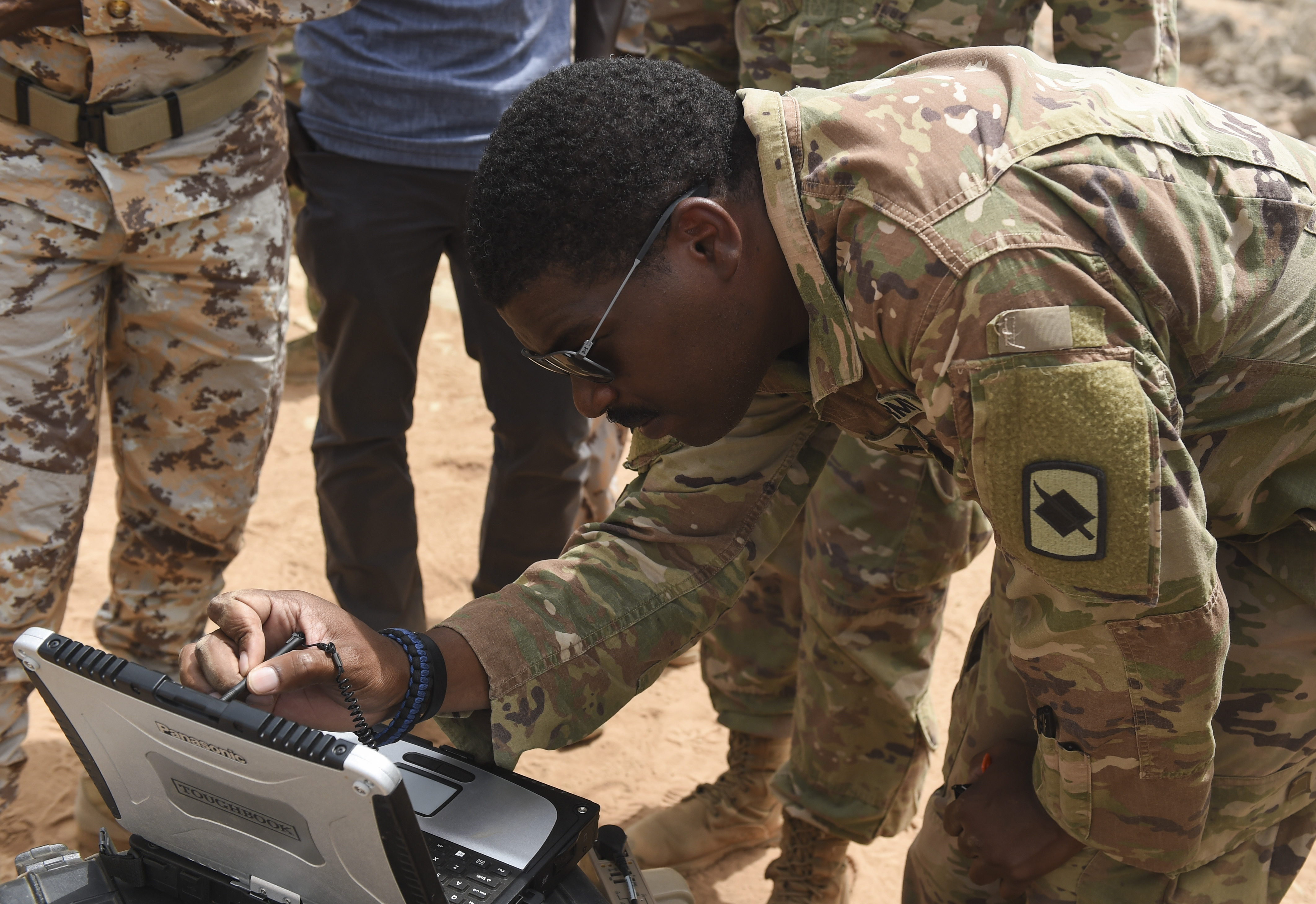 U.S. Army Sgt. Michael Martin, assigned to the 1st Battalion, 153rd Infantry Regiment, Task Force Warrior, an associated unit of Combined Joint Task Force - Horn of Africa, demonstrates the use of a ground control station in an airfield in southern Djibouti, Aug. 21, 2017. The demonstration provided an opportunity to familiarize Djibouti Armed Forces members with the unmanned aerial vehicle system, clear up confusion about the RQ-11 Raven and other remotely piloted aircraft, and show the safe operation of the Raven. (U.S. Air Force photo by Staff Sgt. Eboni Prince)