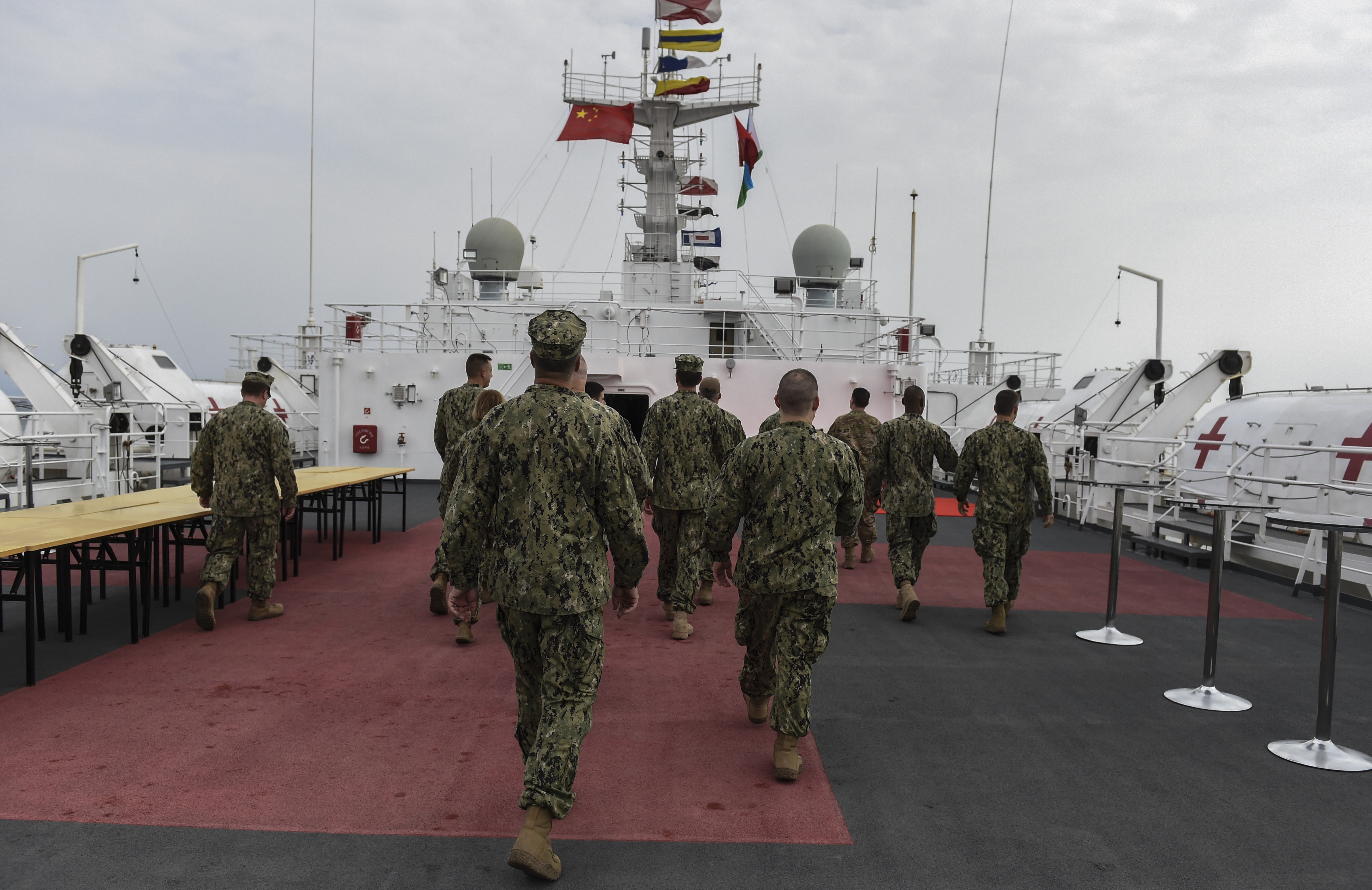 U.S. Navy Sailors assigned to Camp Lemonnier walk on the deck of the Chinese hospital ship, Ark Peace, in the Port of Djibouti, August 28, 2017. Medical personnel from Camp Lemonnier visited the Ark Peace and received a tour from Chinese medical personnel to highlight the ship's capabilities. (U.S. Air Force photo by Staff Sgt. Eboni Prince)