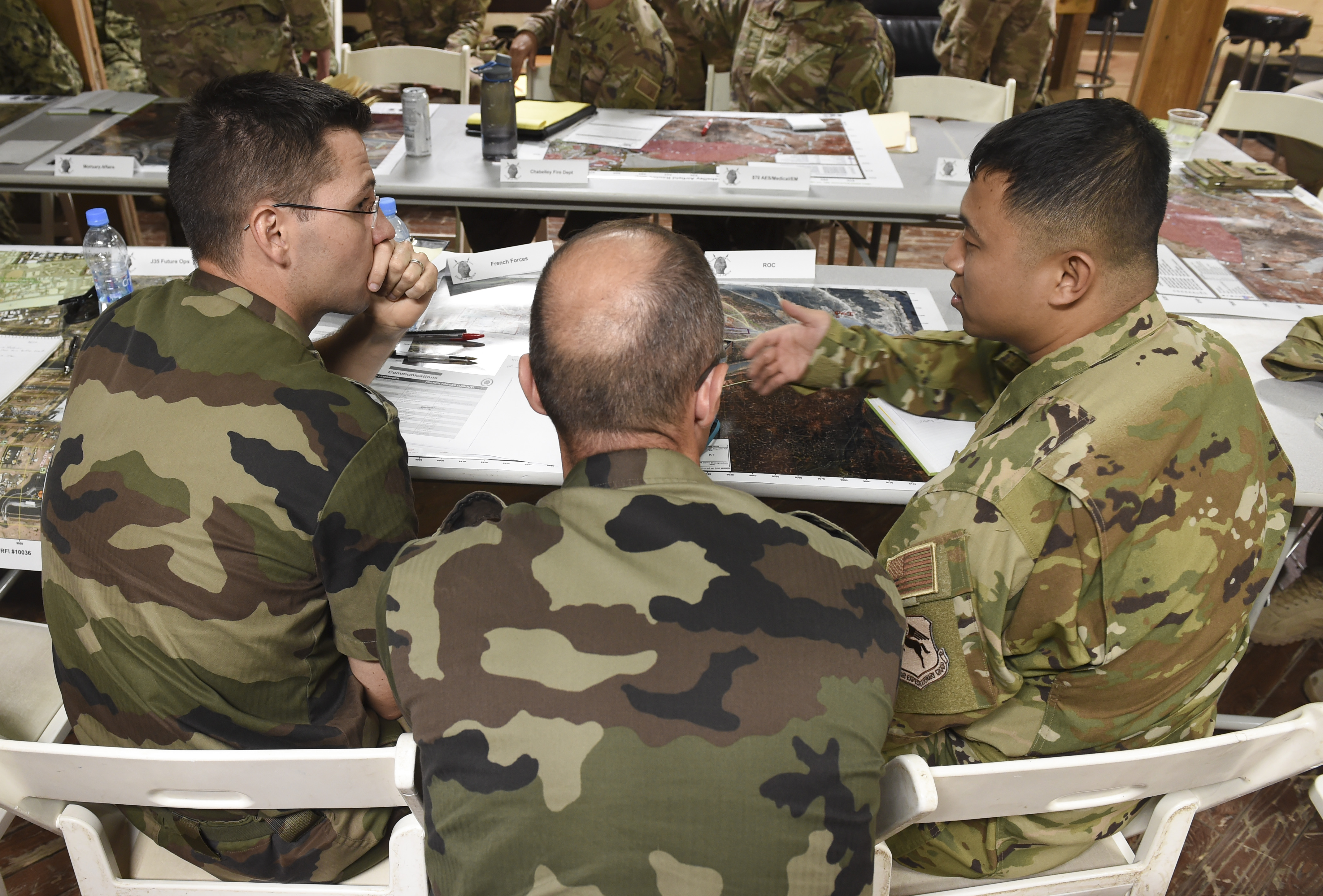 U.S. Air Force Maj. Manh Pham (right), assigned to Combined Joint Task Force-Horn of Africa, speaks with members of the French Army during a bilateral tabletop exercise focusing on multiple unit support and response to a mass casualty incident at Camp Lemonnier, Sept. 6, 2017. The tabletop exercise was a first step in preparation for future bilateral exercises with French forces to further strengthen military relationships and medical-response capabilities in Djibouti. (U.S. Air Force photo by Staff Sgt. Eboni Prince)
