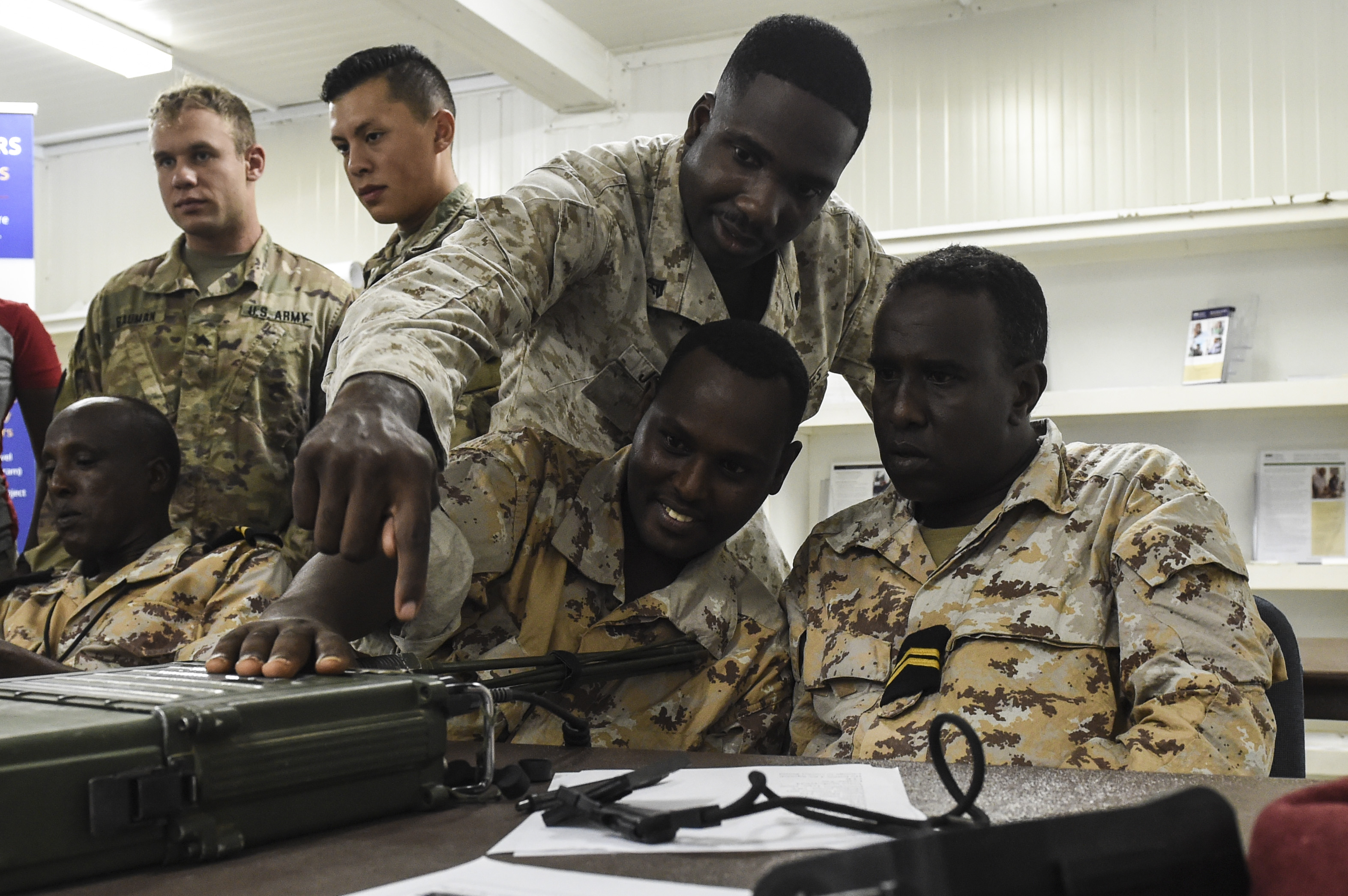 U.S. Marine Corps Cpl. Vickson Joseph, a field radio operator assigned to the Combined Joint Task Force-Horn of Africa communications directorate, demonstrates the proper use of a Harris radio during a three-day best practices sharing session with Djibouti Armed Forces at Camp Lemonnier, Oct. 3, 2017. With the aid of slide show presentations, multiple practical exercises and hands-on demonstrations, the tactical communications personnel showcased how thy use the radios and exchanged information about standard operating procedures with FAD personnel. (U.S. Air Force photo by Staff Sgt. Eboni Prince)