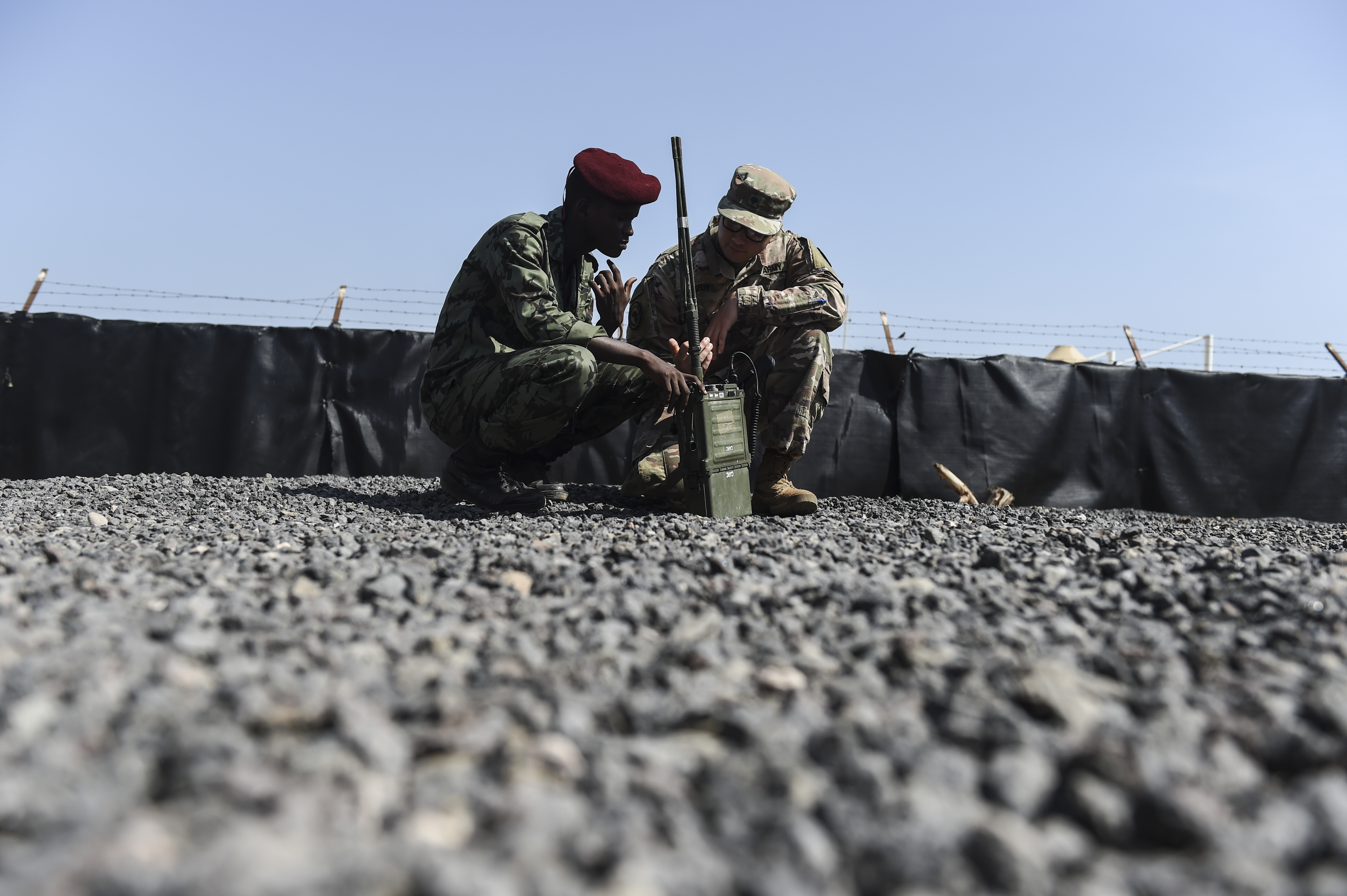 U.S. Army Spc. Matthew Jousselin, a radio operator assigned to the Combined Joint Task Force-Horn of Africa communications directorate, assists a member of the Djibouti Armed Forces with a hands-on demonstration during a three-day best practices sharing session with Djibouti Armed Forces at Camp Lemonnier, Oct. 3, 2017. Best-practice sharing events like these help East African partners to strengthen their defense capabilities, capacity, and coordination to enable them to provide for their own security, combat transnational threats, and respond to crises.  (U.S. Air Force photo by Staff Sgt. Eboni Prince)