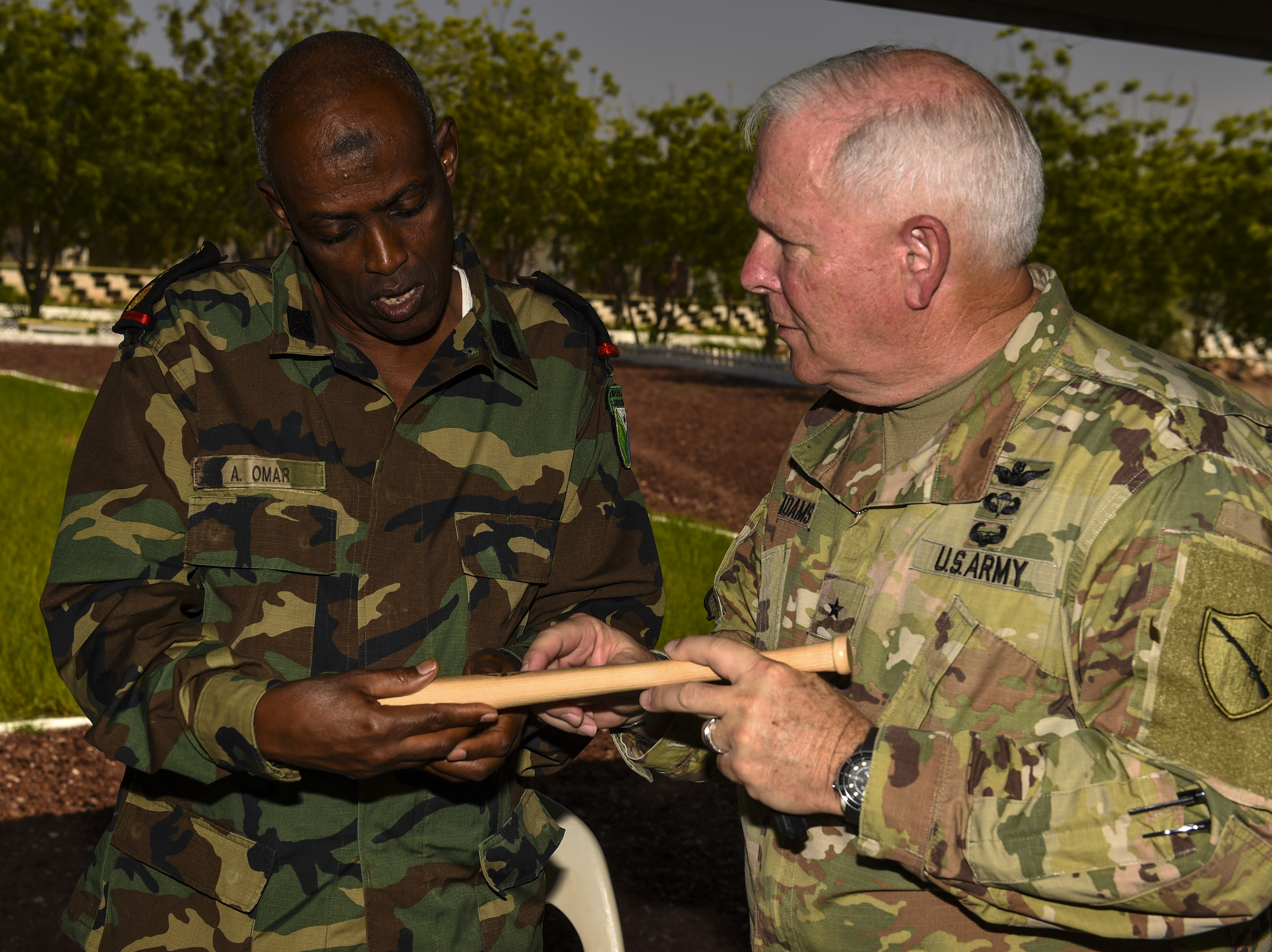 U.S. Army National Guard Brig. Gen. Benjamin Adams III (right), Kentucky National Guard deputy adjutant general, gives a miniature Louisville slugger bat to Djibouti Armed Force (FAD) Lt. Col. A. Omar during a State Partnership Program (SPP) visit to the FAD military training center at Holhol, Djibouti, Nov. 14, 2017. The SPP is a joint U.S. Department of Defense program that matches a state's National Guard with a nation to promote enduring, mutually beneficial security relationships. (U.S. Air Force photo by Staff Sgt. Timothy Moore)