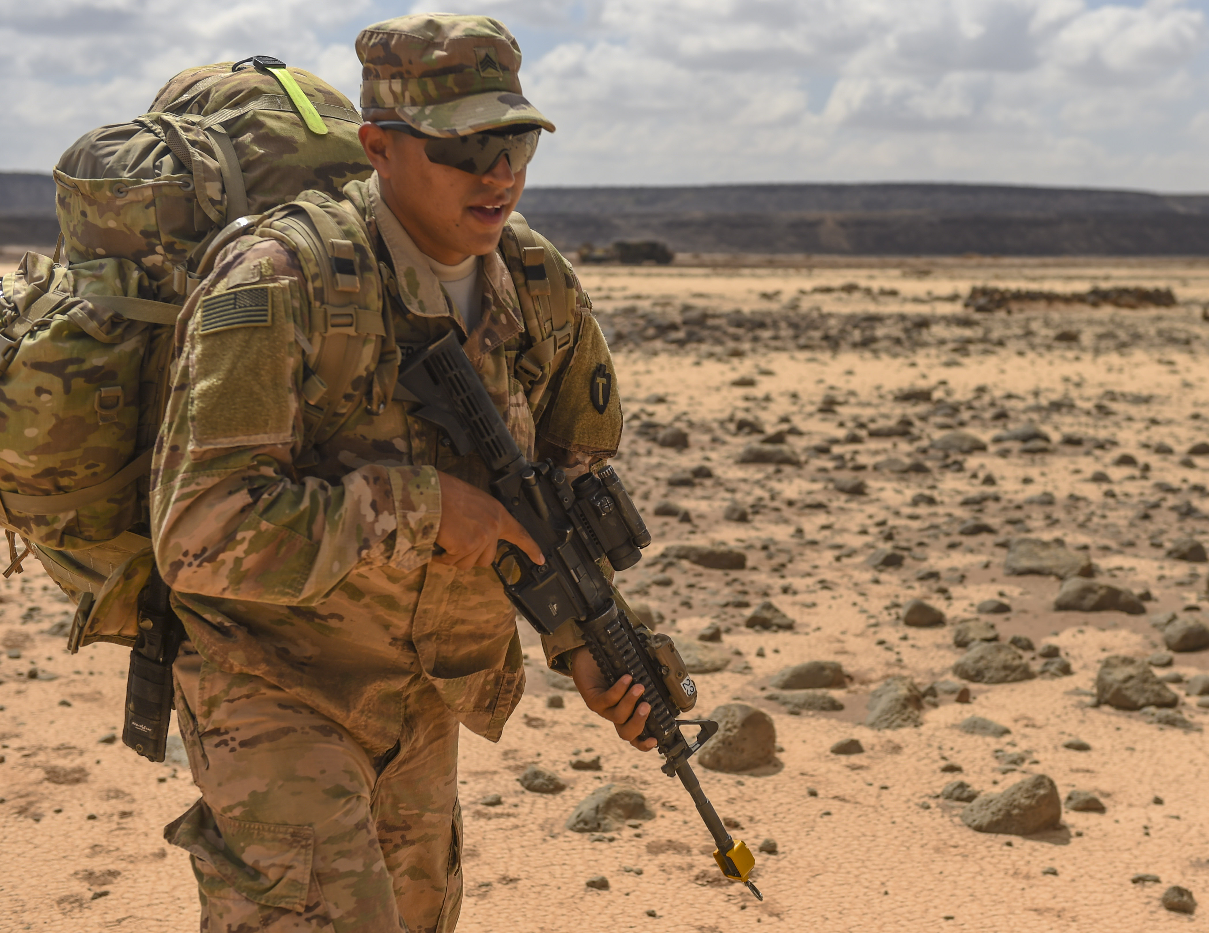 U.S. Army National Guard Sgt. Gabriel Mancera, 3rd Battalion, 144th Infantry Regiment, Task Force Bayonet, carries his rucksack to his defensive position during the first day of a French Desert Commando Course at the Djibouti Range Complex near Arta, Djibouti, Nov. 26, 2017. The 12-day course will expose service members to the fundamentals of desert combat, survival, and troop movements while also bridging language and cultural barriers between the French and American troops. (U.S. Air Force photo by Staff Sgt. Timothy Moore)