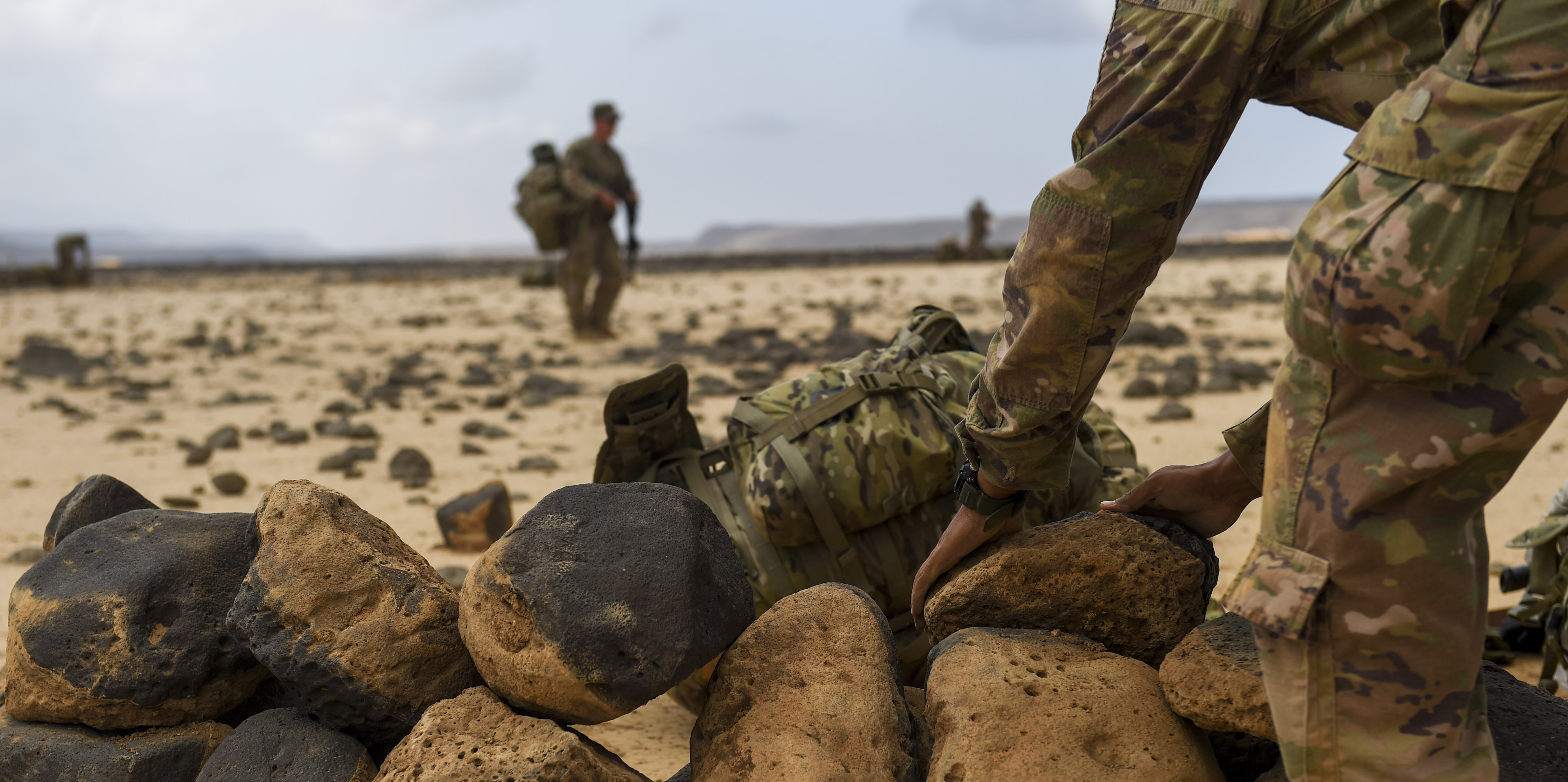 U.S. Army National Guard Spc. Keifer Davis, 3rd Battalion, 144th Infantry Regiment, Task Force Bayonet, stacks rocks as he sets up a defensive position on the first day of a French Desert Commando Course at the Djibouti Range Complex near Arta, Djibouti, Nov. 26, 2017. The 12-day course will expose service members to the fundamentals of desert combat, survival, and troop movements while also bridging language and cultural barriers between the French and American troops. (U.S. Air Force photo by Staff Sgt. Timothy Moore)