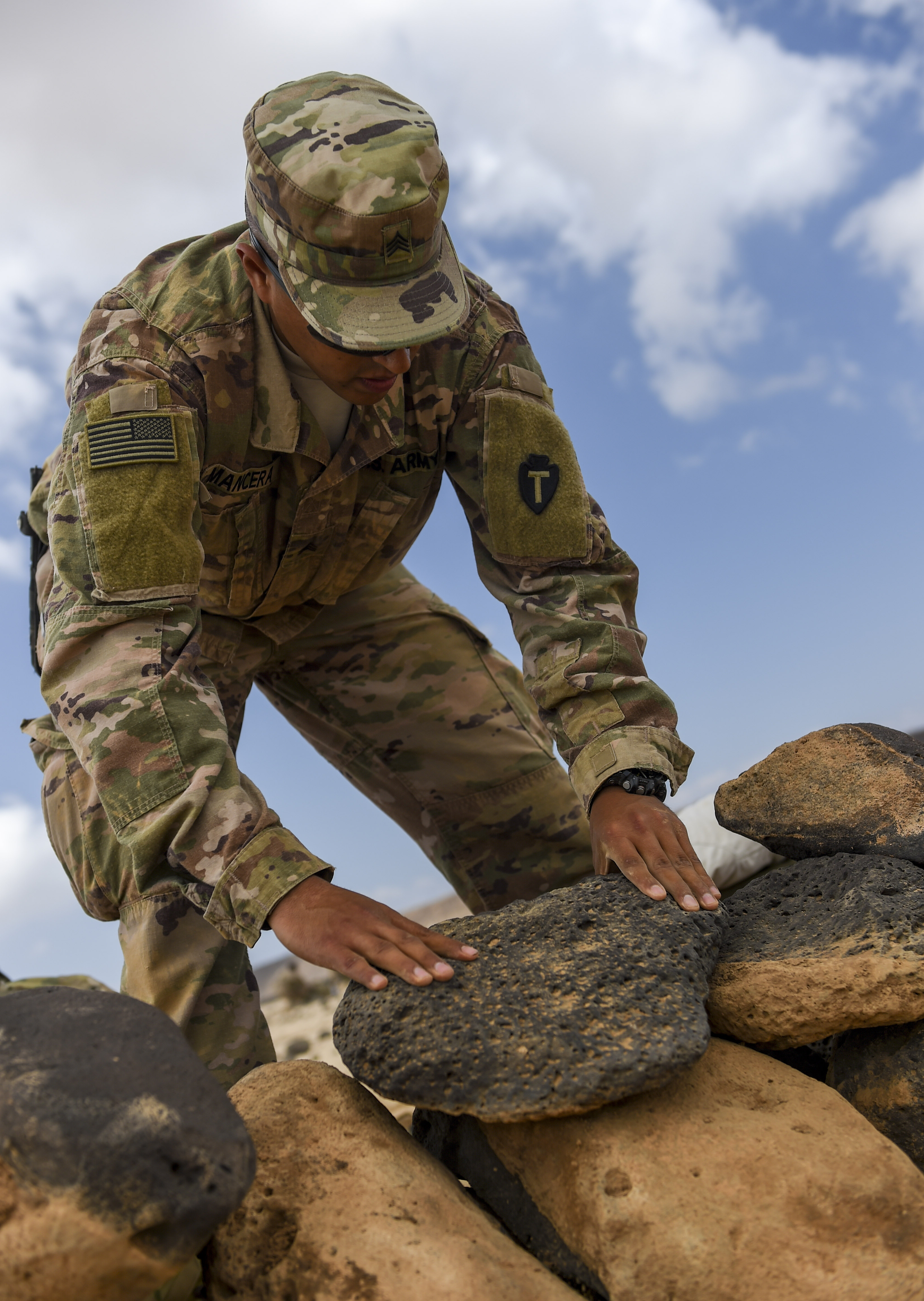 U.S. Army National Guard Sgt. Gabriel Mancera, 3rd Battalion, 144th Infantry Regiment, Task Force Bayonet, stacks rocks as he sets up a defensive position on the first day of a French Desert Commando Course at the Djibouti Range Complex near Arta, Djibouti, Nov. 26, 2017. The 12-day course will expose service members to the fundamentals of desert combat, survival, and troop movements while also bridging language and cultural barriers between the French and American troops. (U.S. Air Force photo by Staff Sgt. Timothy Moore)