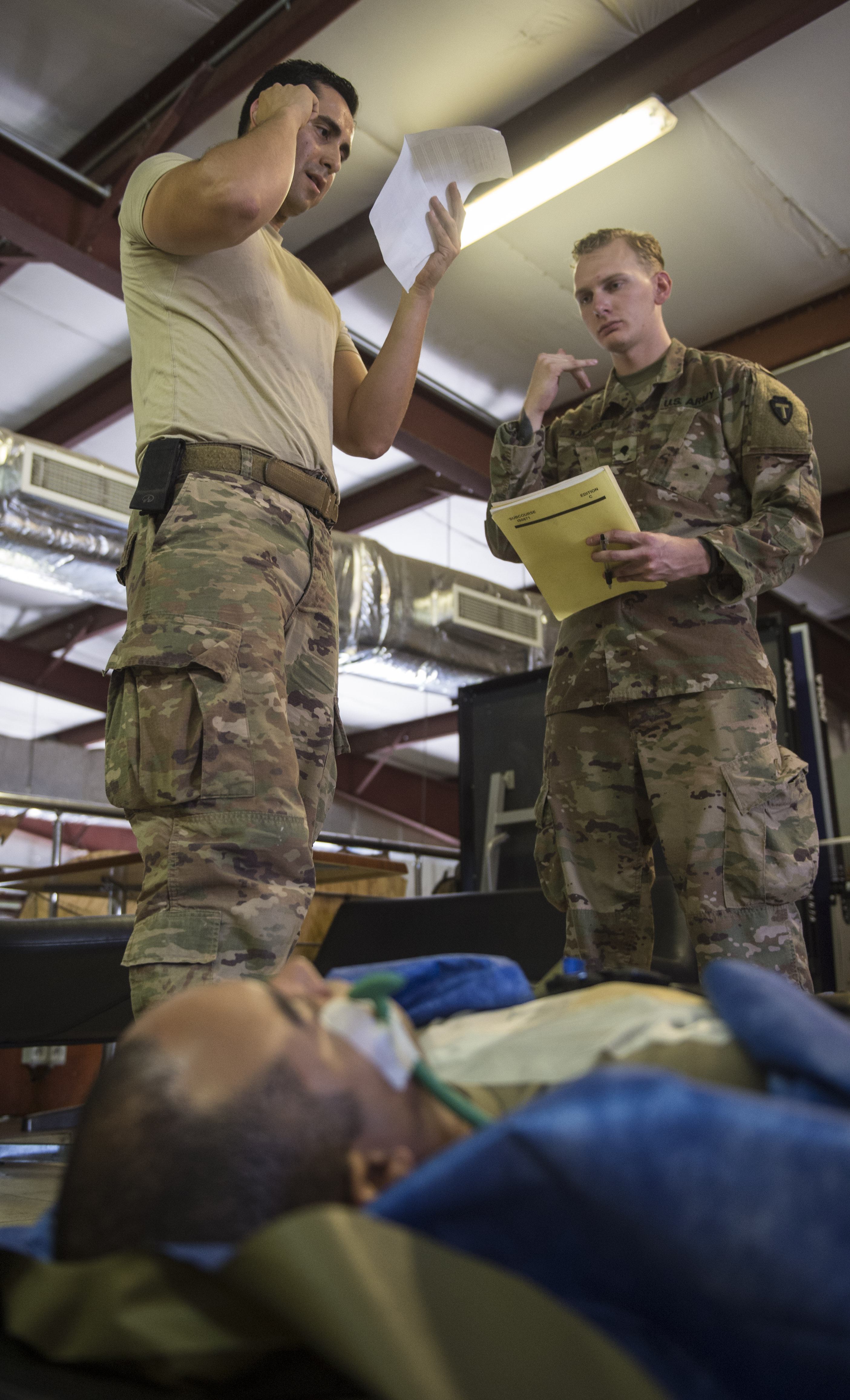 U.S. Air Force Staff Sgt. Julio Rojas (left), assigned to the 870th Aeromedical Evacuation Squadron, simulates calling for a medical evacuation as U.S. Army Spc. Alexander Kahanek, an instructor assigned to the 3rd Battalion, 144th Infantry Regiment Task Force Bayonet, attached to the Combined Joint Task Force – Horn of Africa, observes the final assessment of a U.S. Army Combat Lifesaver Course held at Camp Lemonnier, Djibouti, Dec. 1, 2017. The five-day course focused on teaching students how to administer lifesaving tactical medical care to wounded service members on the battlefield. (U.S. Air Force photo by Staff Sgt. Timothy Moore)