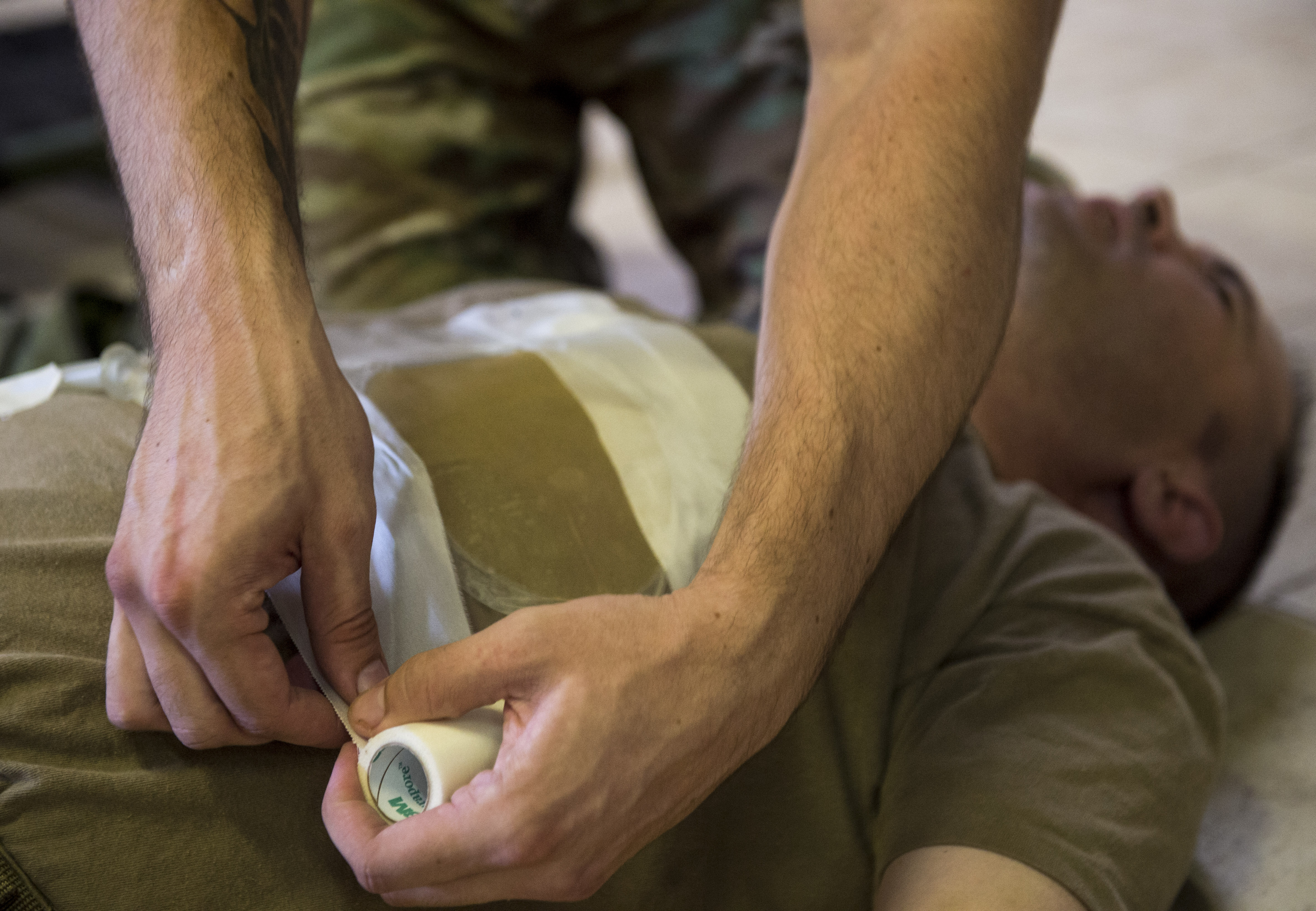 U.S. Air Force Airman 1st Class Antonio Espinoza, assigned to the Combined Joint Task Force - Horn of Africa Communications Directorate, seals the edges of a simulated open chest wound during the final assessment of a U.S. Army Combat Lifesaver Course held at Camp Lemonnier, Djibouti, Dec. 1, 2017. The five-day course focused on teaching students how to administer lifesaving tactical medical care to wounded service members on the battlefield. (U.S. Air Force photo by Staff Sgt. Timothy Moore)