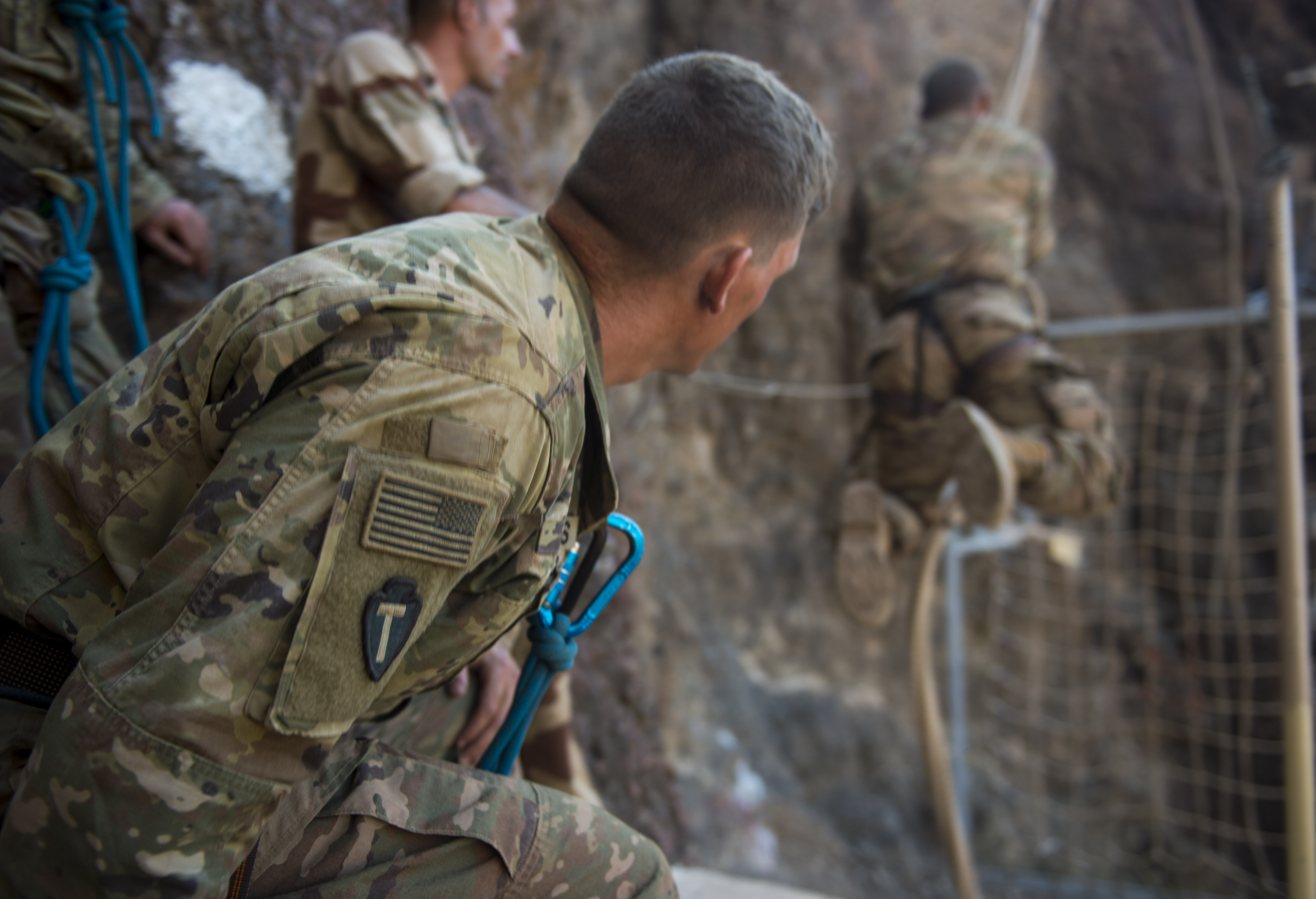 A U.S. Army Soldier assigned to the 3rd Battalion, 144th Infantry Regiment Task Force Bayonet, attached to the Combined Joint Task Force - Horn of Africa, observes a teammate swing to a cargo net during the mountain obstacle portion of the French Desert Commando Course held at Arta, Djibouti, Dec. 3, 2017. Thirty U.S. service members participated in the obstacle course alongside French marines assigned to the 5th Overseas Interarms Regiment, Djibouti.(U.S. Air Force photo by Staff Sgt. Timothy Moore)