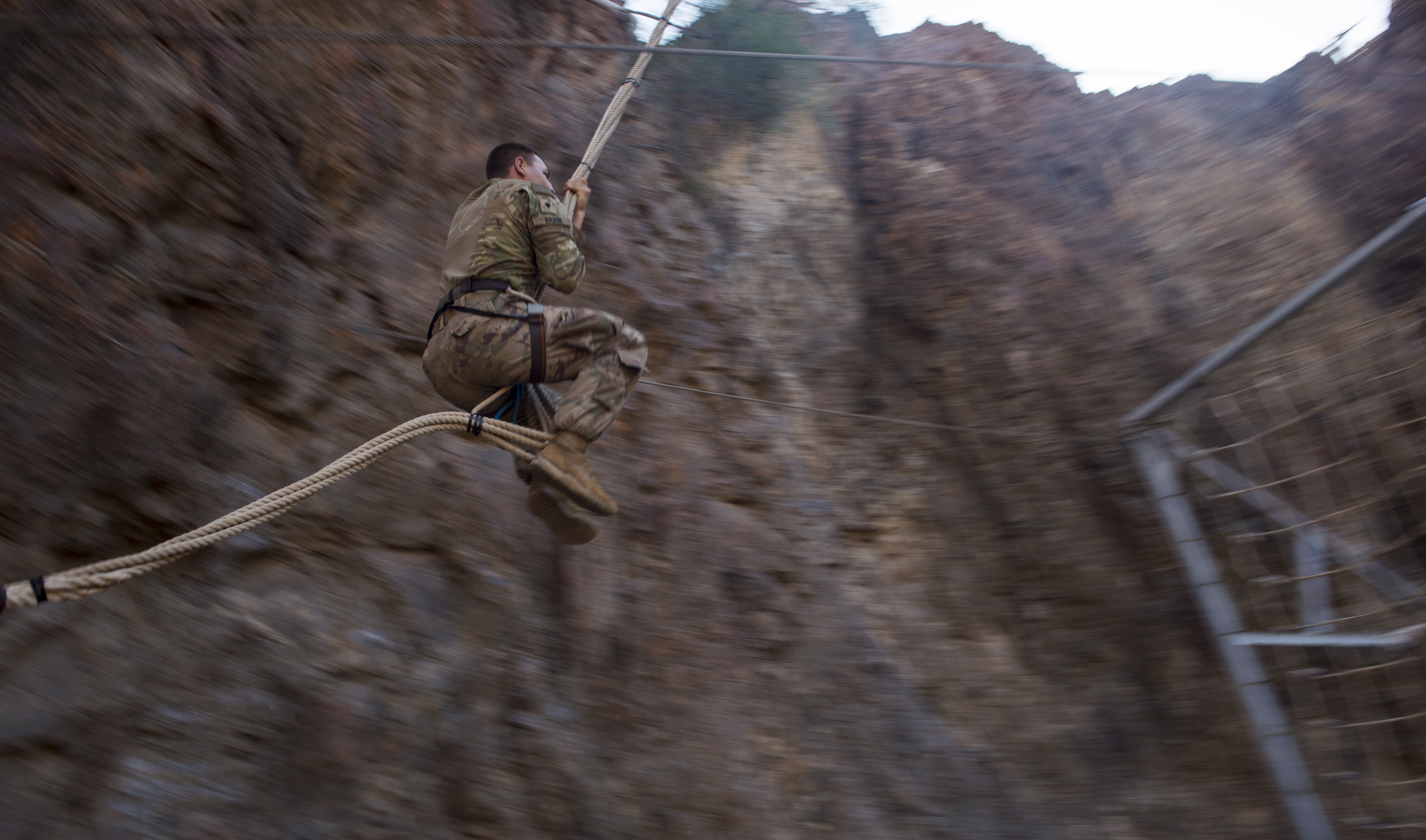 A U.S. Army Soldier assigned to Combined Joint Task Force - Horn of Africa swings to a cargo net during the mountain obstacle portion of the French Desert Command Course held at Arta, Djibouti, Dec. 3, 2017. Thirty U.S. service members participated in the obstacle course alongside French marines assigned to the 5th Overseas Interarms Regiment, Djibouti. (U.S. Air Force photo by Staff Sgt. Timothy Moore)