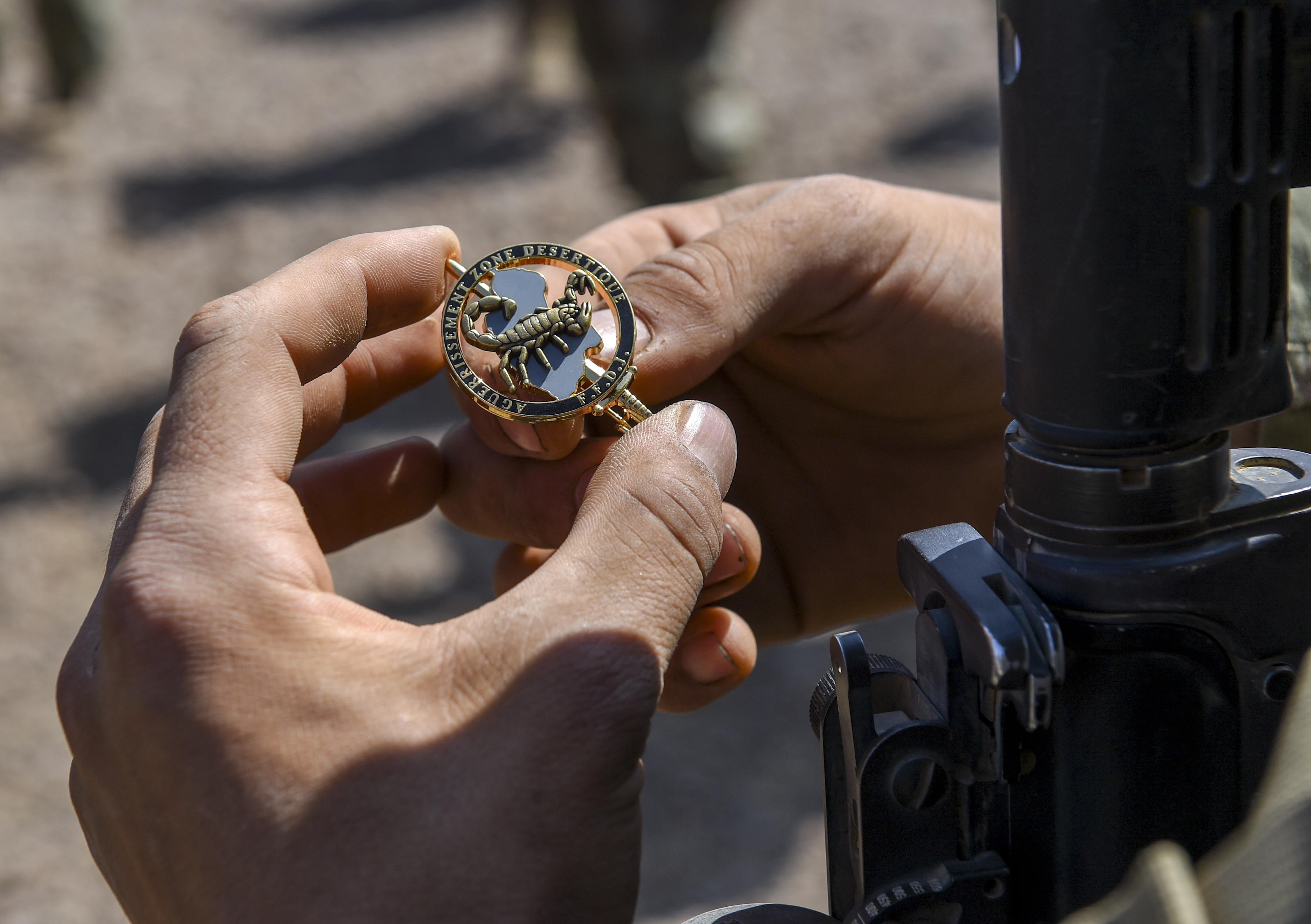 A U.S. Army Soldier assigned to Combined Joint Task Force - Horn of Africa (CJTF-HOA) looks at his French Desert Commando Course pin after the graduation ceremony near Ali Sabieh, Djibouti, Dec. 7, 2017. U.S. service members assigned to CJTF-HOA participated in the 12-day course, in which they learned the fundamentals of desert combat, survival, and troop movements while also bridging language and cultural barriers between French and American troops. (U.S. Air Force photo by Staff Sgt. Timothy Moore)