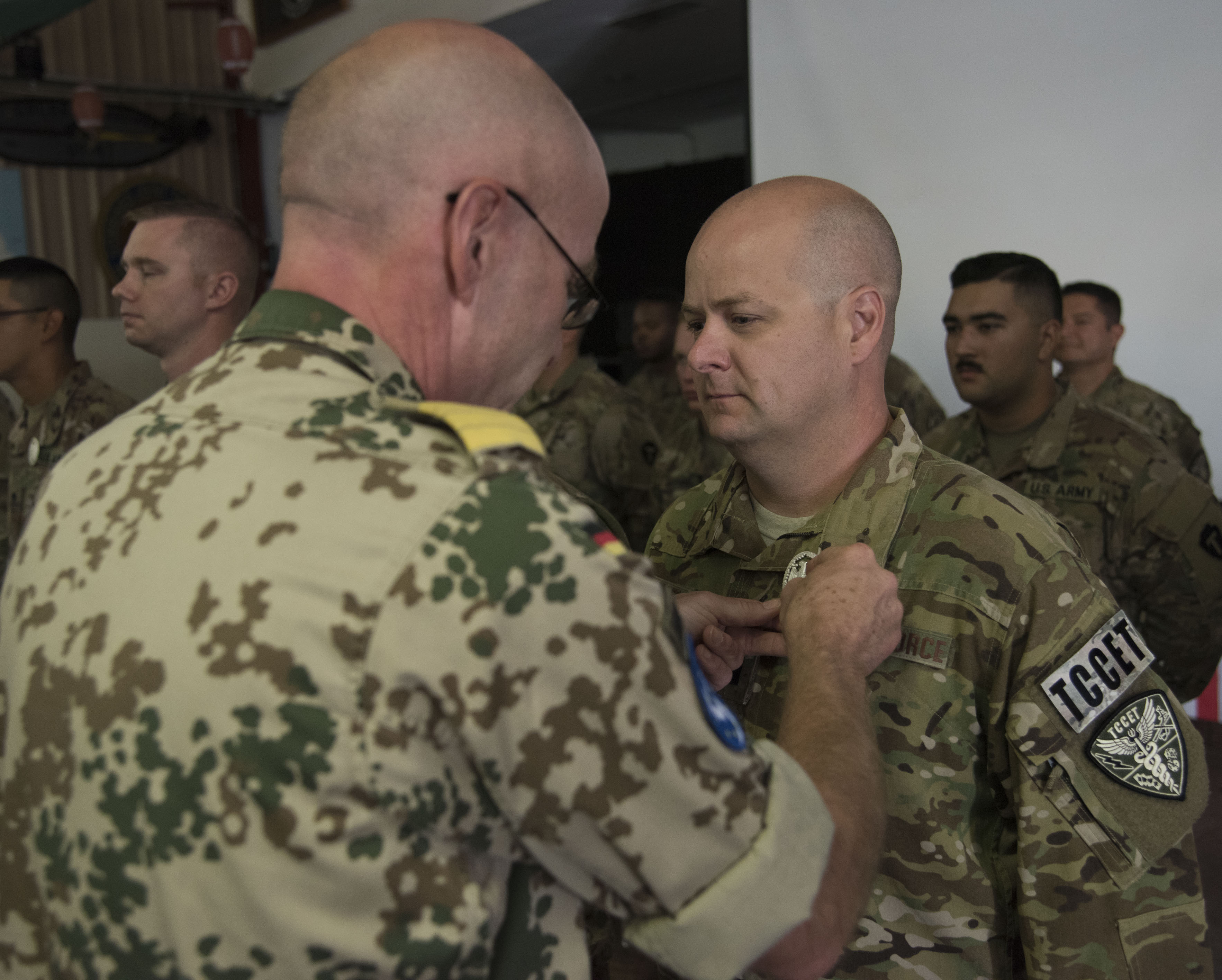 A U.S. Air Force Airman assigned to Combined Joint Task Force-Horn of Africa receives the German Armed Forces Proficiency Badge (GAFPB), a decoration of the Armed Forces of the Federal Republic of Germany, by German commander Axel Schilling at Camp Lemonnier, Djibouti, Dec. 8, 2017. Competitors completed a physical fitness test, uniformed swim, weapons qualification, ruck march, first aid course and chemical warfare course to be awarded the GAFPB, one of the few foreign allied military awards that U.S. service members are authorized to wear. (U.S. Air National Guard photo by Staff Sgt. Allyson L. Manners)