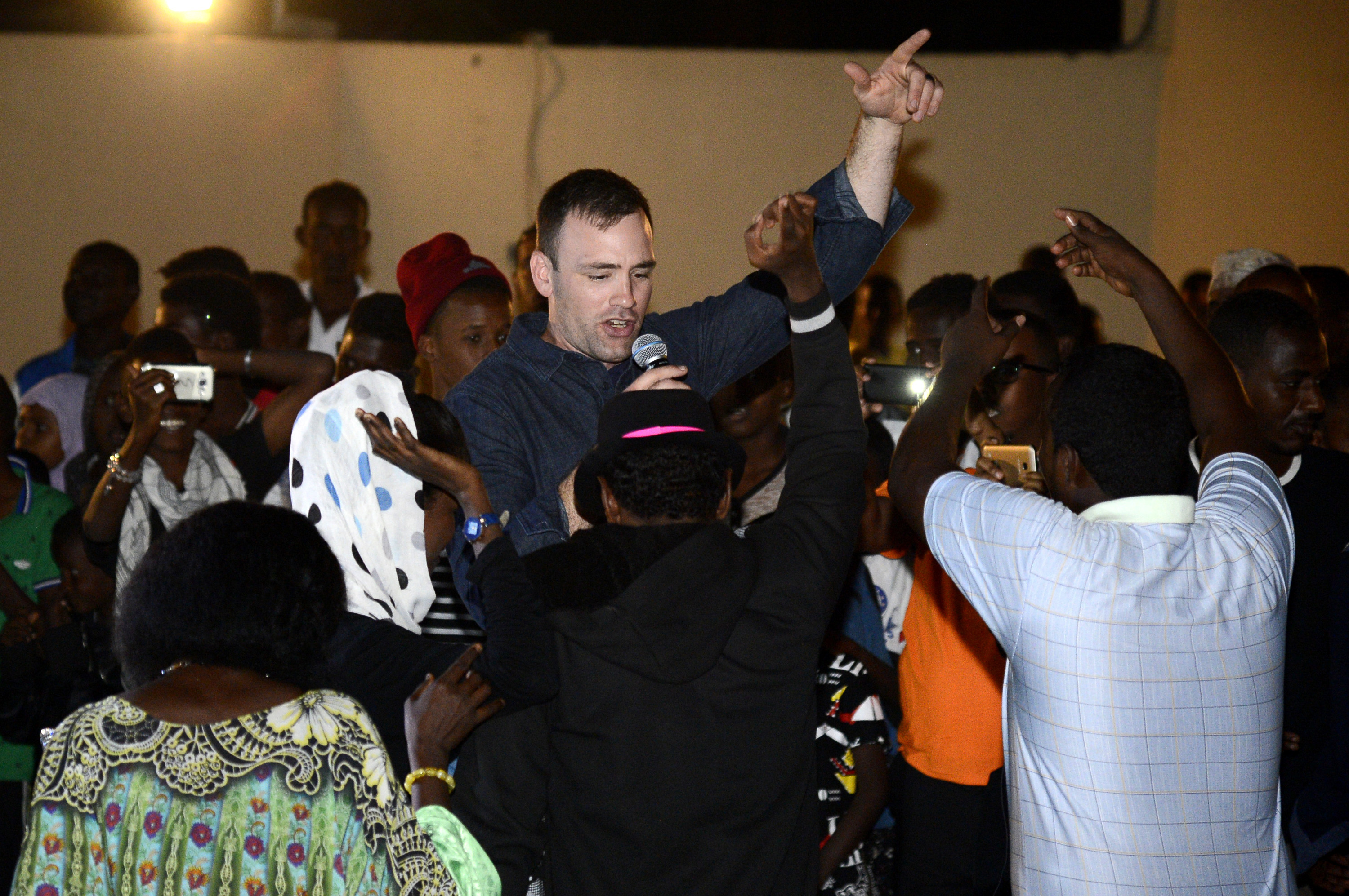 U.S. Air Force Staff Sgt. Craig Larimer, a member of the Air Forces Central Command (AFCENT) Band, sings and dances with Djiboutians during a concert at the Balbala E-Learning Center in Djibouti, January 10, 2018. The AFCENT Band performed at the E-Learning center as part of their two week tour where they held workshops, clinics, and concerts throughout the city of Djibouti. (U.S. Navy Photo by Mass Communication Specialist 2nd Class Timothy M. Ahearn)